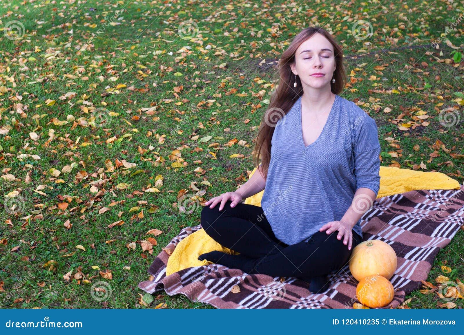 有格子花呢披肩的怀孕的瑜伽妇女和南瓜画象在秋天在草,呼吸,舒展,静止停放 室外,森林