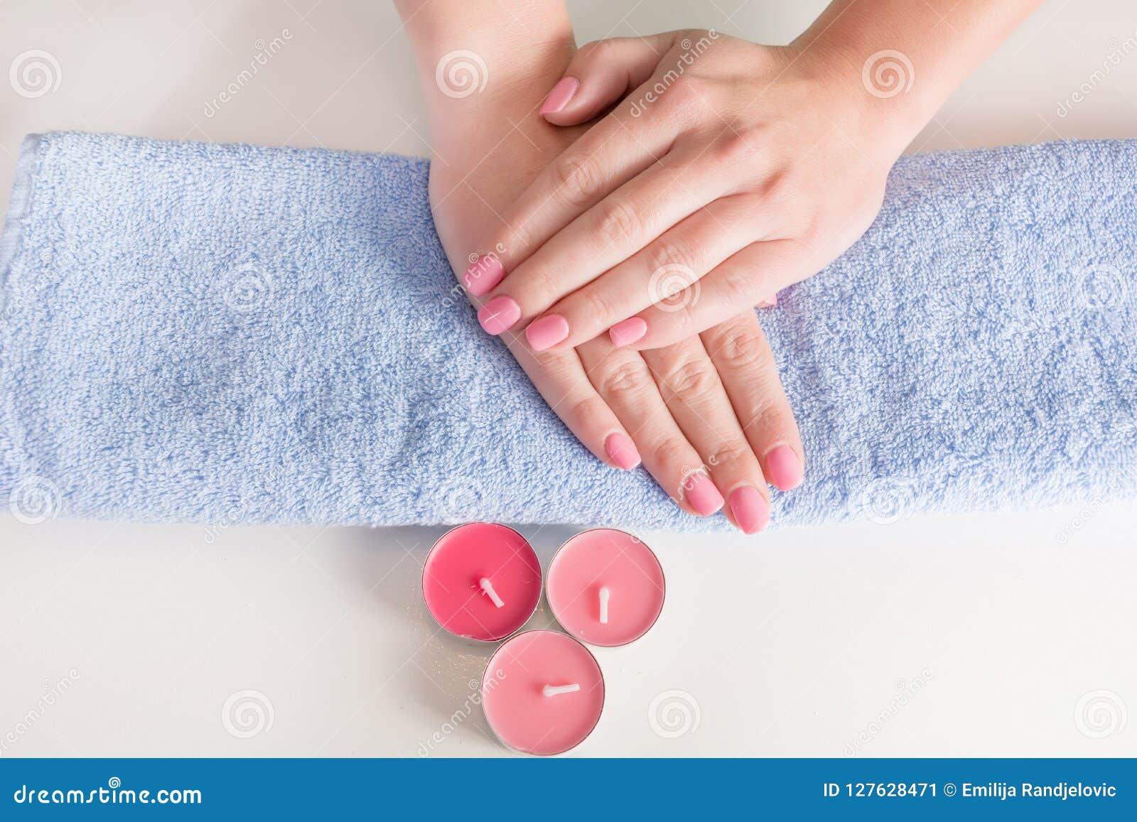 有桃红色修指甲的柔和妇女手在钉子