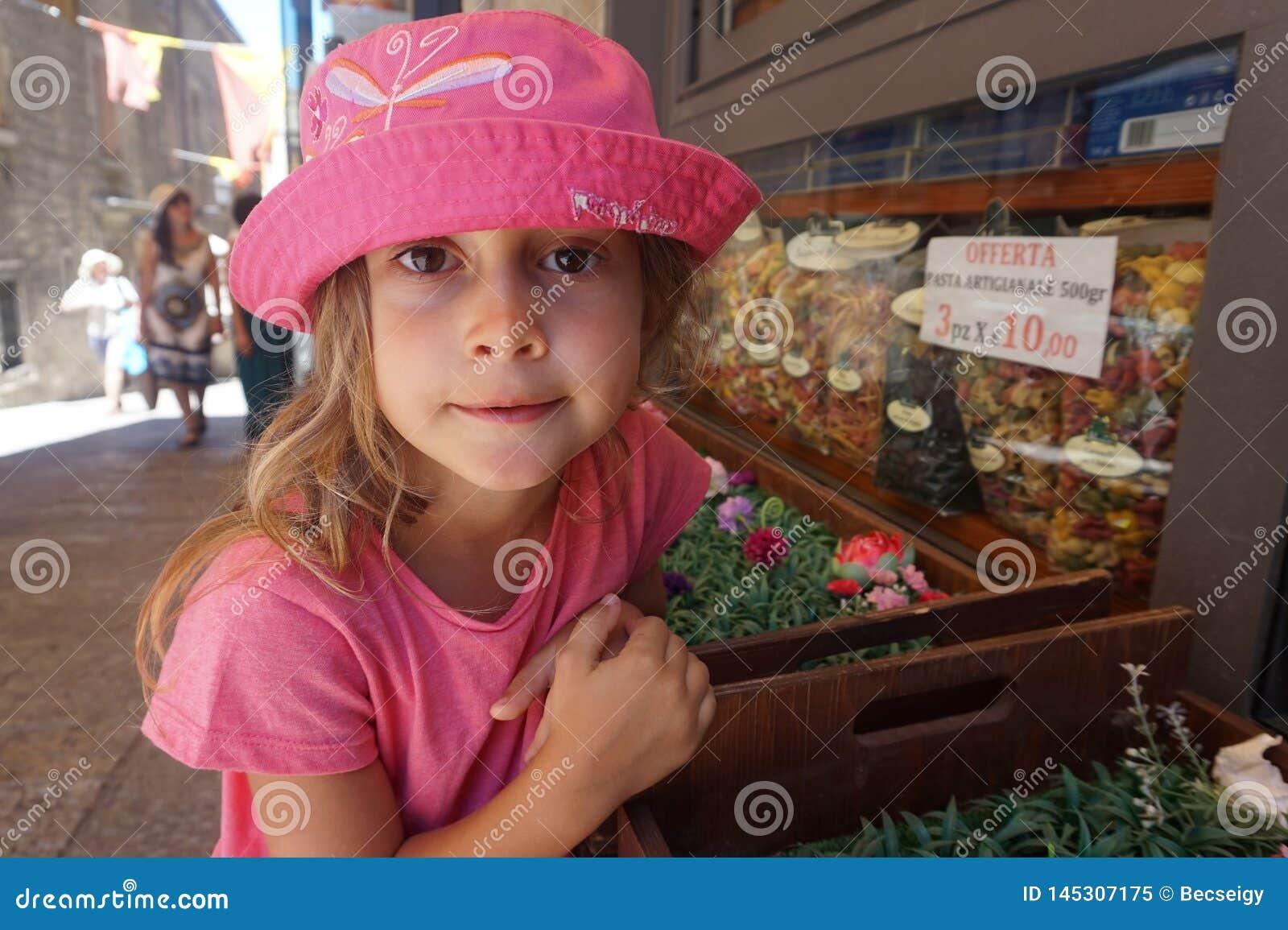 有桃红色帽子的在杂货店前面,圣马力诺女孩