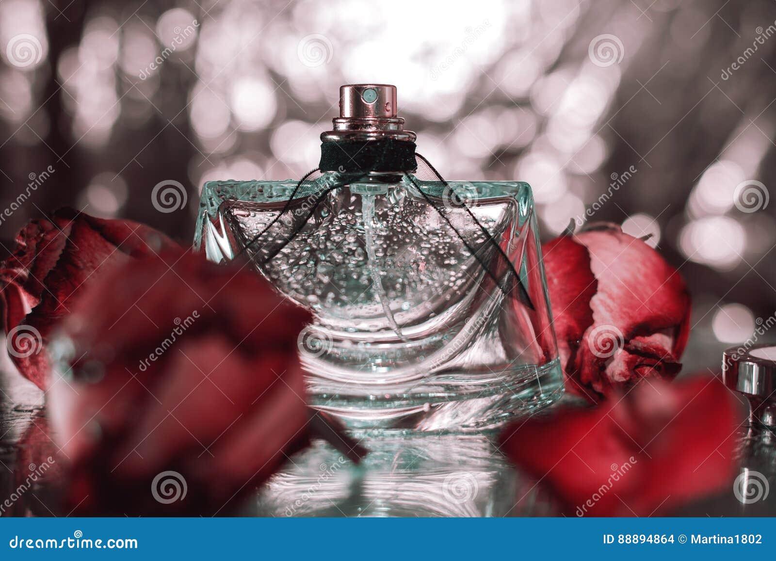 有桃红色花玫瑰的香水瓶