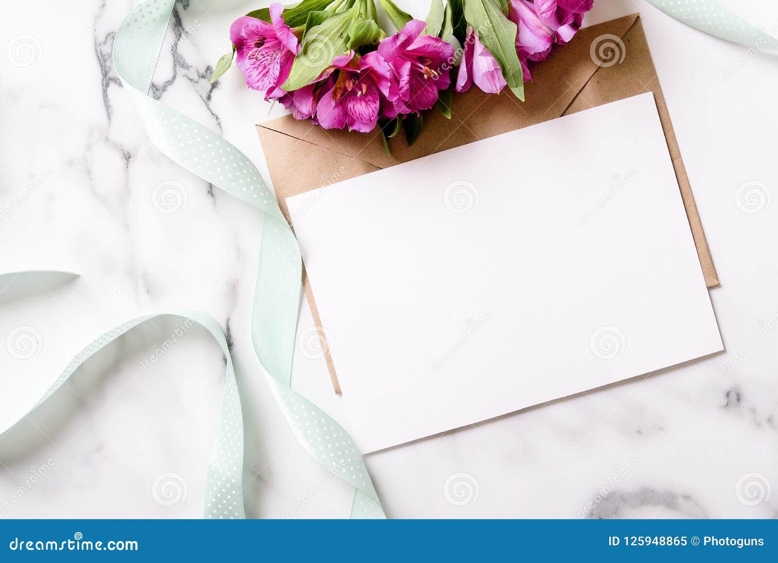 有桃红色花的大理石书桌,明信片,卡拉服特信封,麻线,棉花分支,与拷贝空间的邀请卡片您的文本的