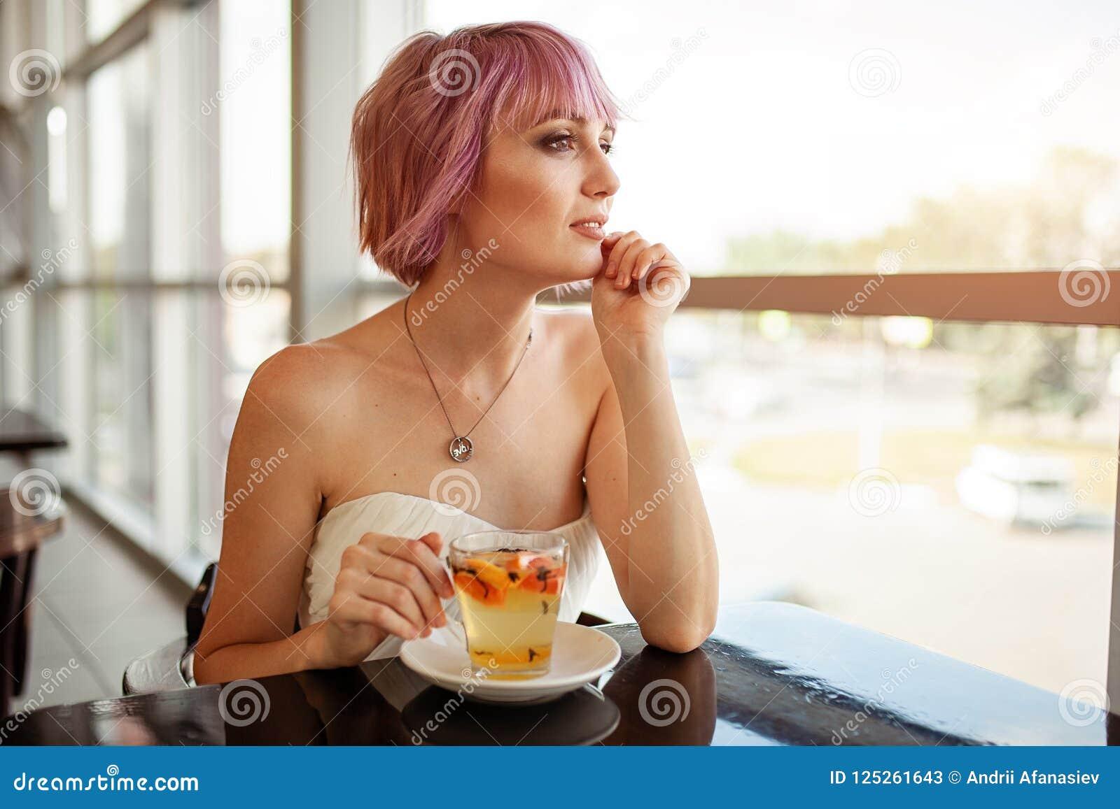 有桃红色被绘的头发的一个美丽的女孩在餐馆坐在窗口饮用的果子茶和看附近梦想向前