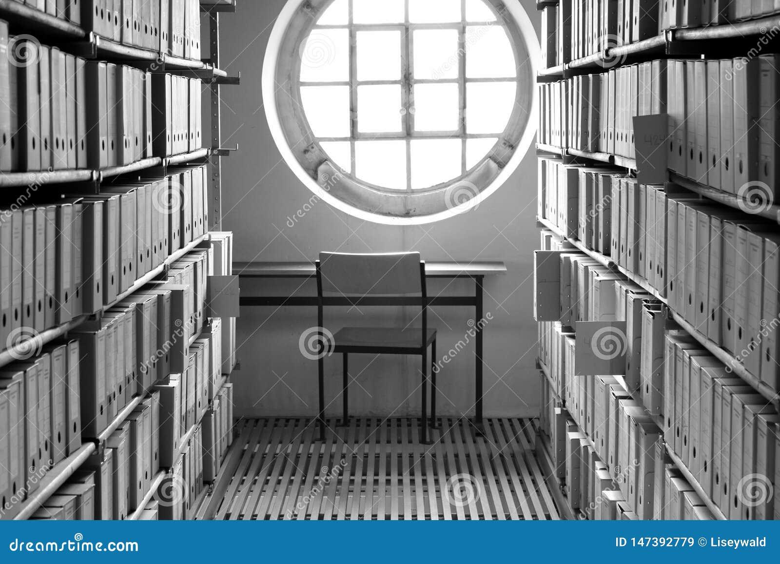 有桌的在书柜和公里围拢的一个晴朗的窗口下的职场和椅子档案箱子