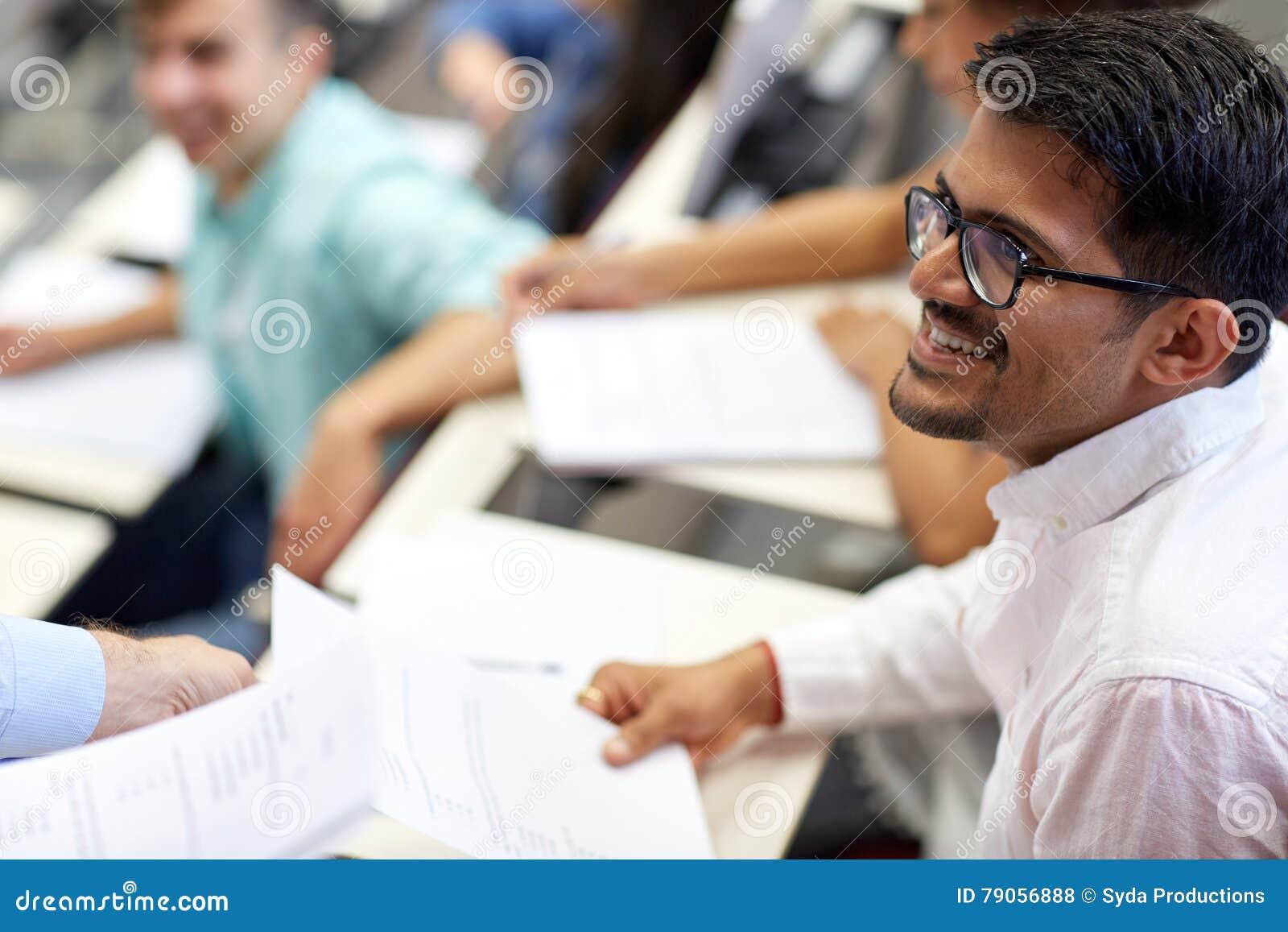 有检查测试或赠送品的愉快的学生在演讲