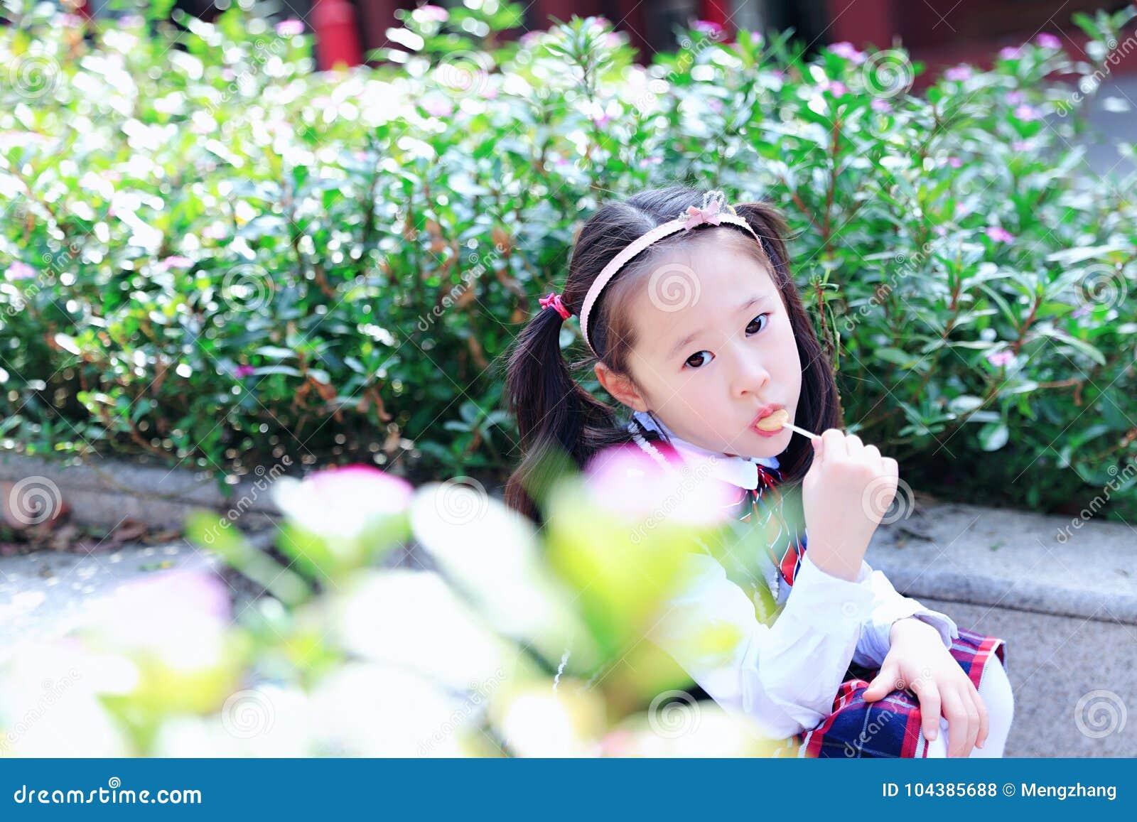 有棒棒糖逗人喜爱的亚洲矮小的美好的女孩戏剧的小女孩秋天在城市公园