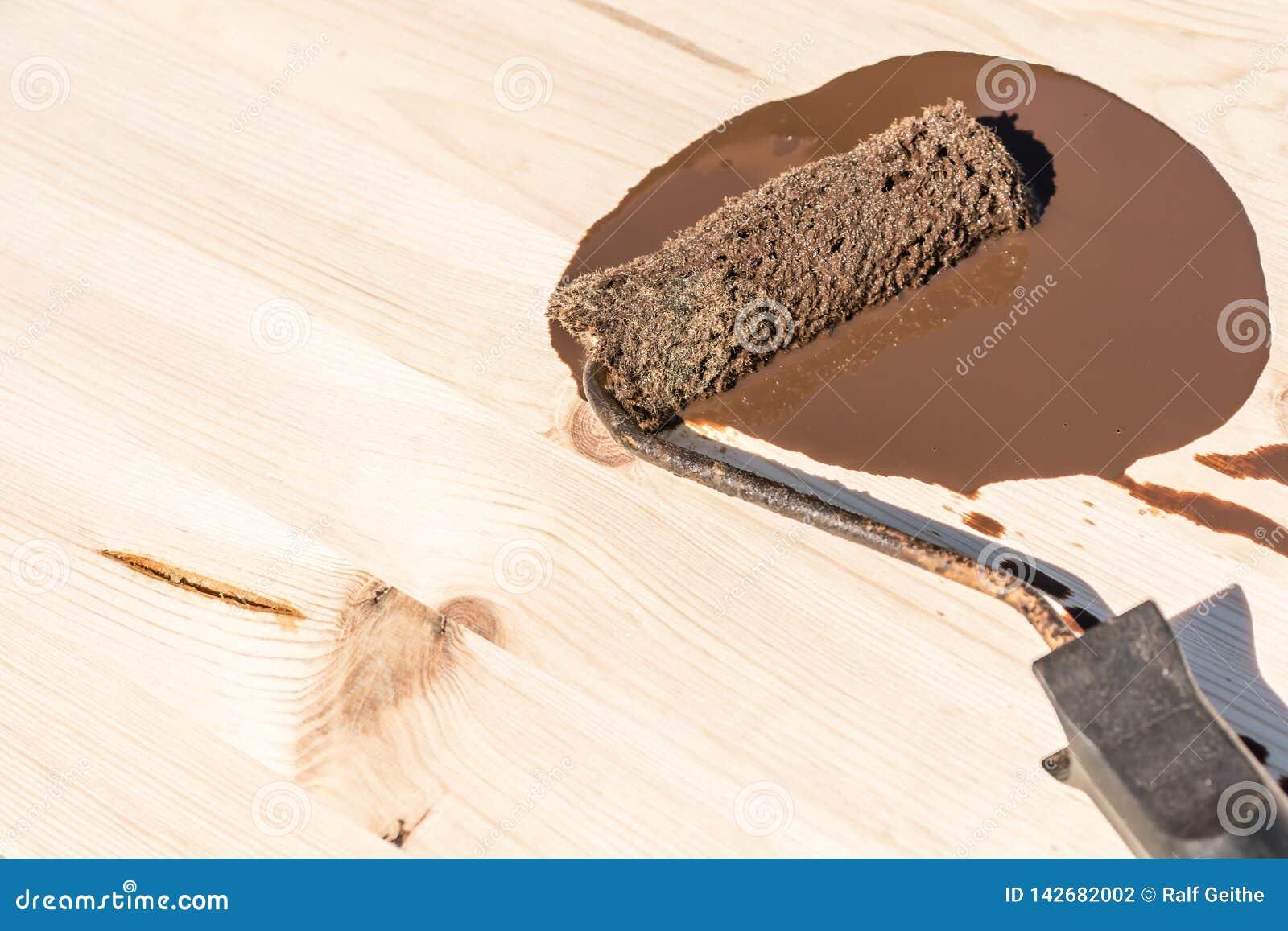 有棕色木污点谎言的漆滚筒在一个木板
