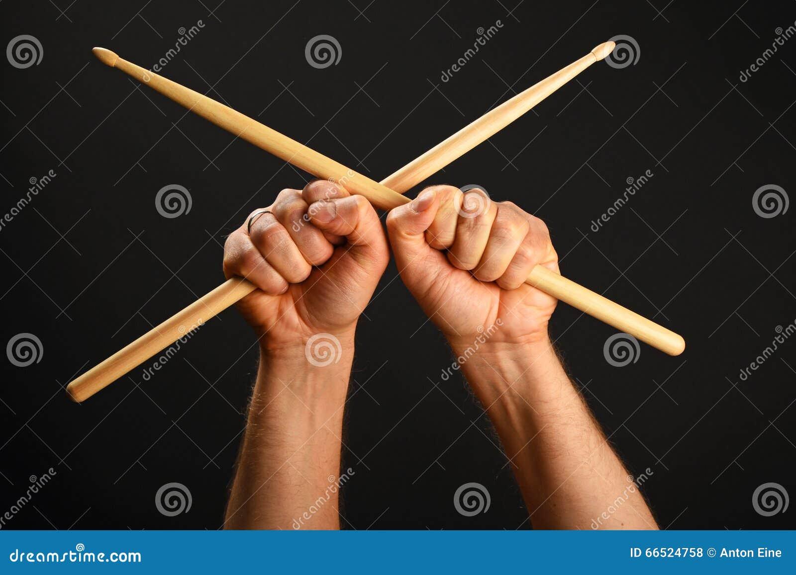 有横渡的鼓槌的两只手在黑色