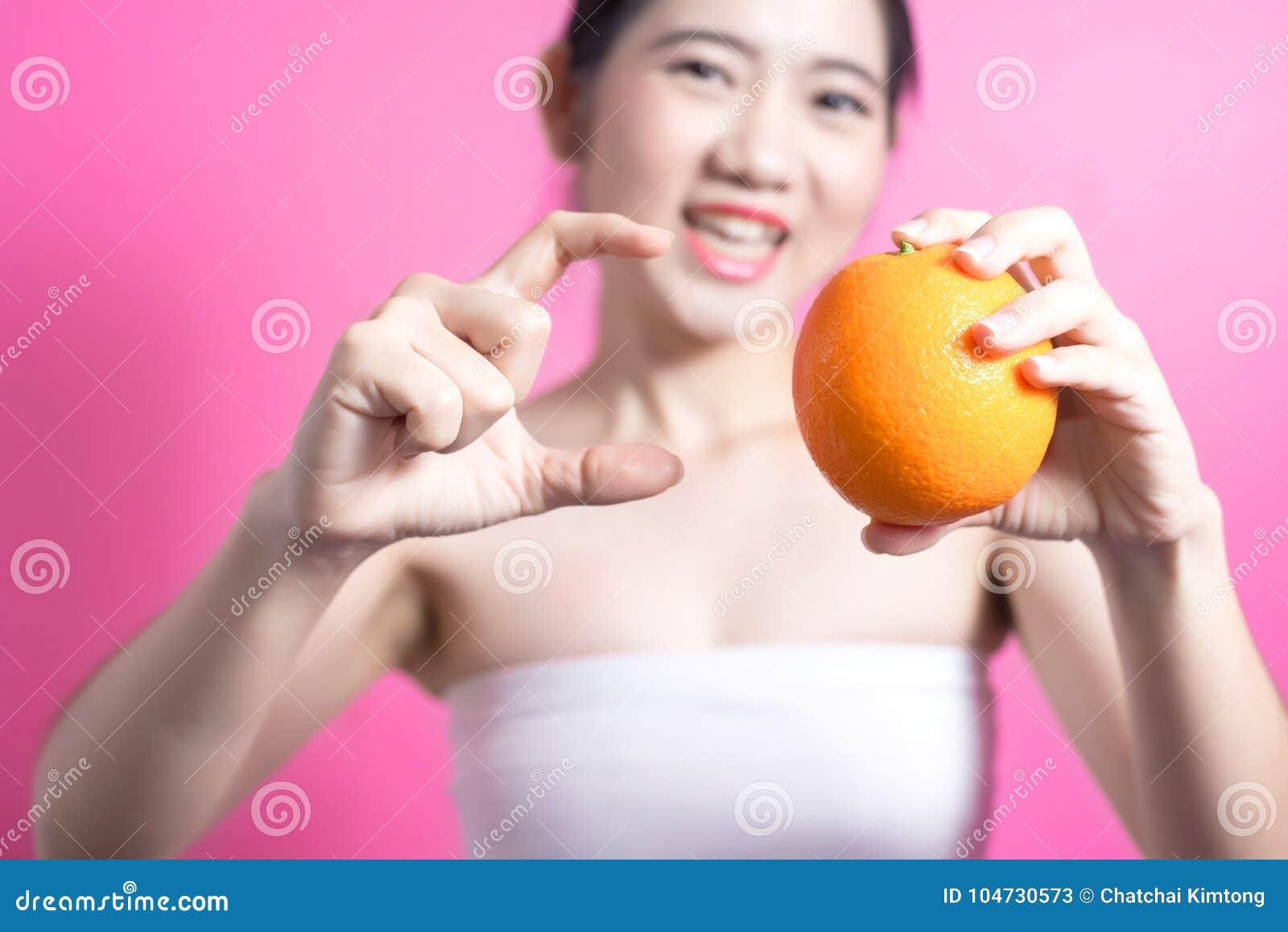 有橙色概念的亚裔妇女 微笑和拿着桔子的她 秀丽面孔和自然构成 隔绝在桃红色背景