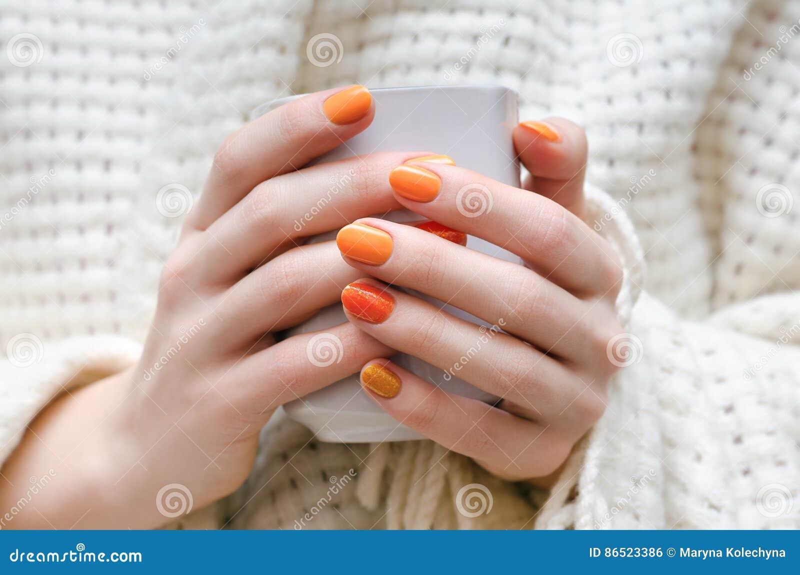 有橙色钉子设计的女性手
