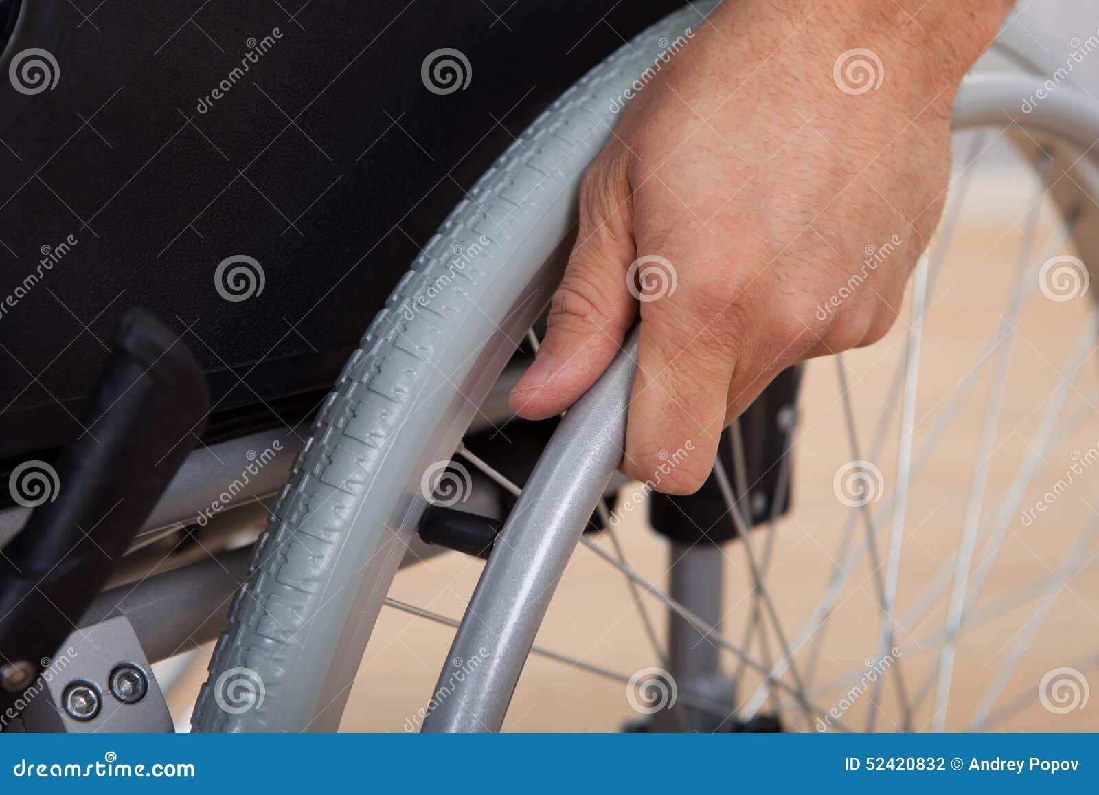 有残障的轮椅人的手按的轮子