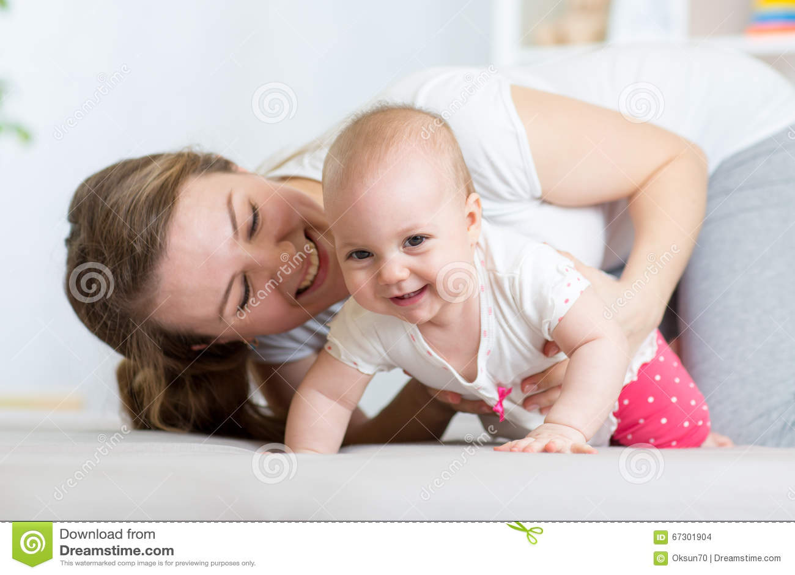 有母亲的滑稽的爬行的女婴在家