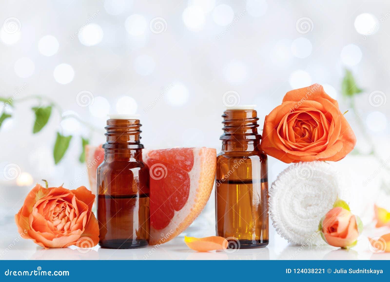 有毛巾、葡萄柚和玫瑰色花的精油瓶在白色桌上 温泉,芳香疗法,健康,秀丽背景