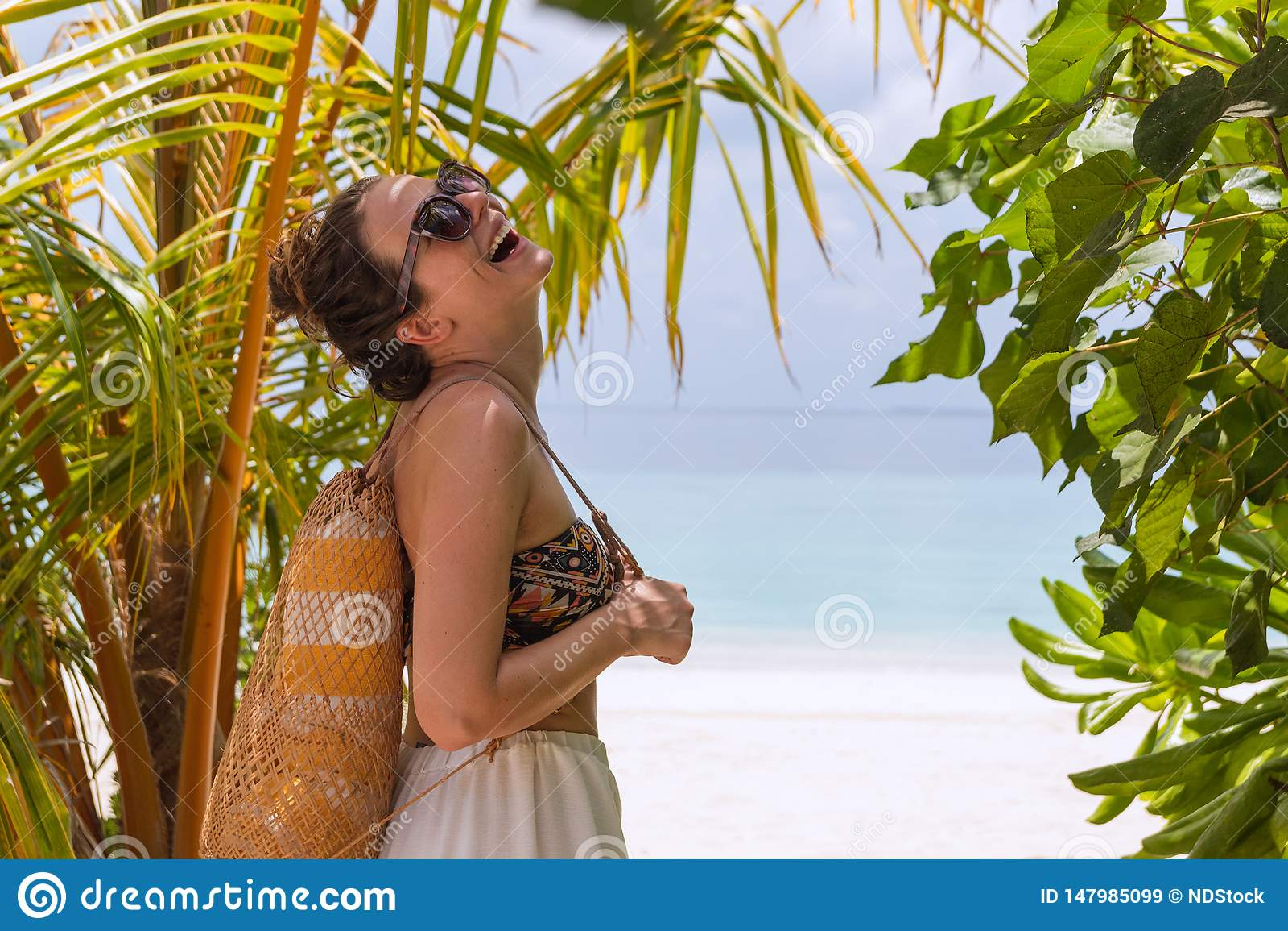 有毛巾的年轻愉快的妇女走到在一个热带目的地的海滩的 笑对照相机