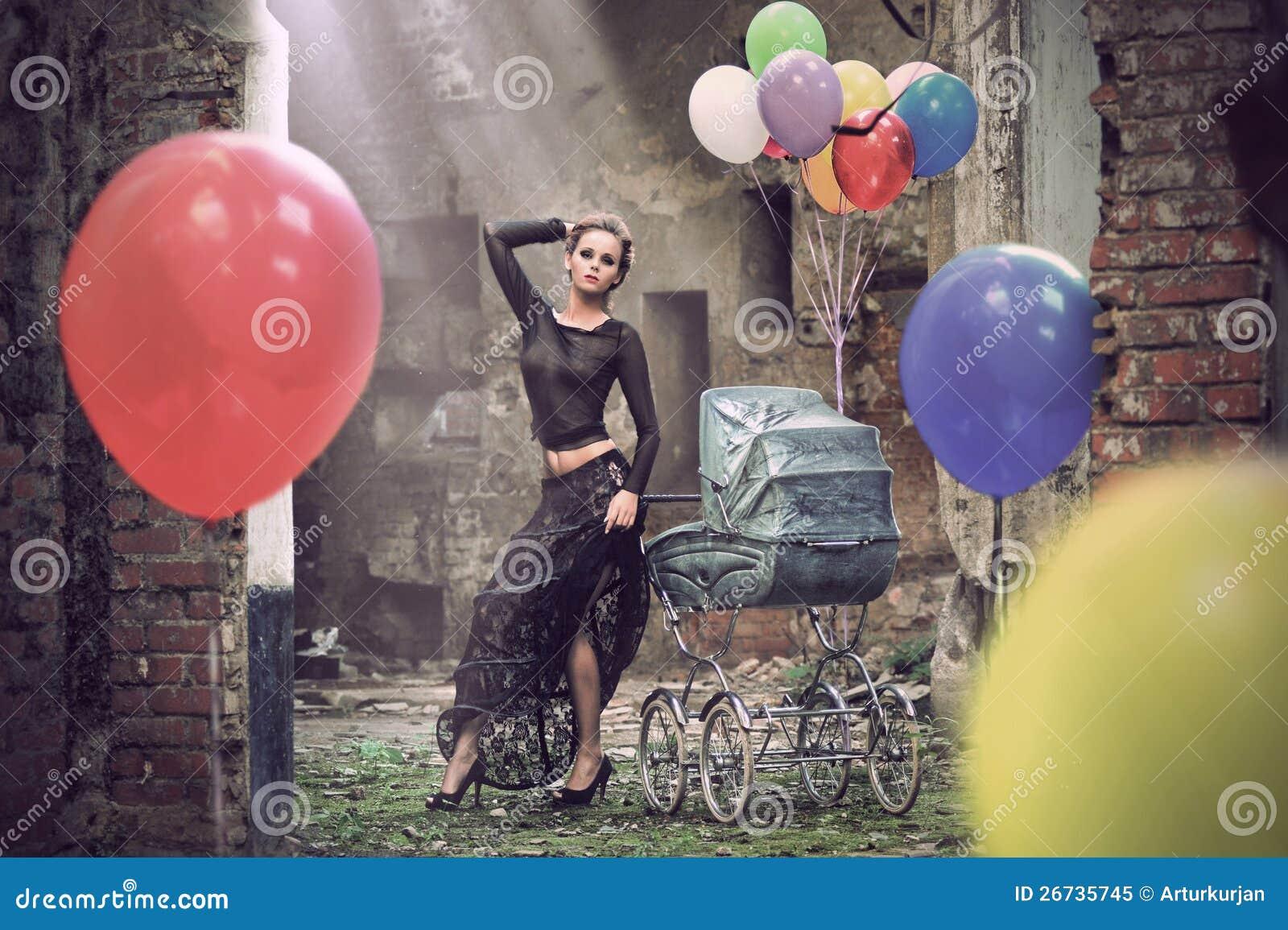 有气球和婴儿车的新性感的妇女