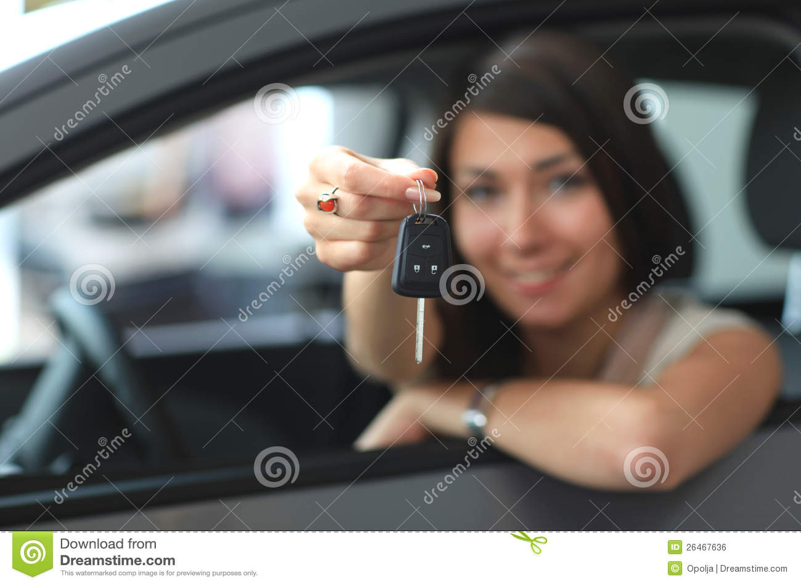 有汽车关键字的愉快的微笑的妇女