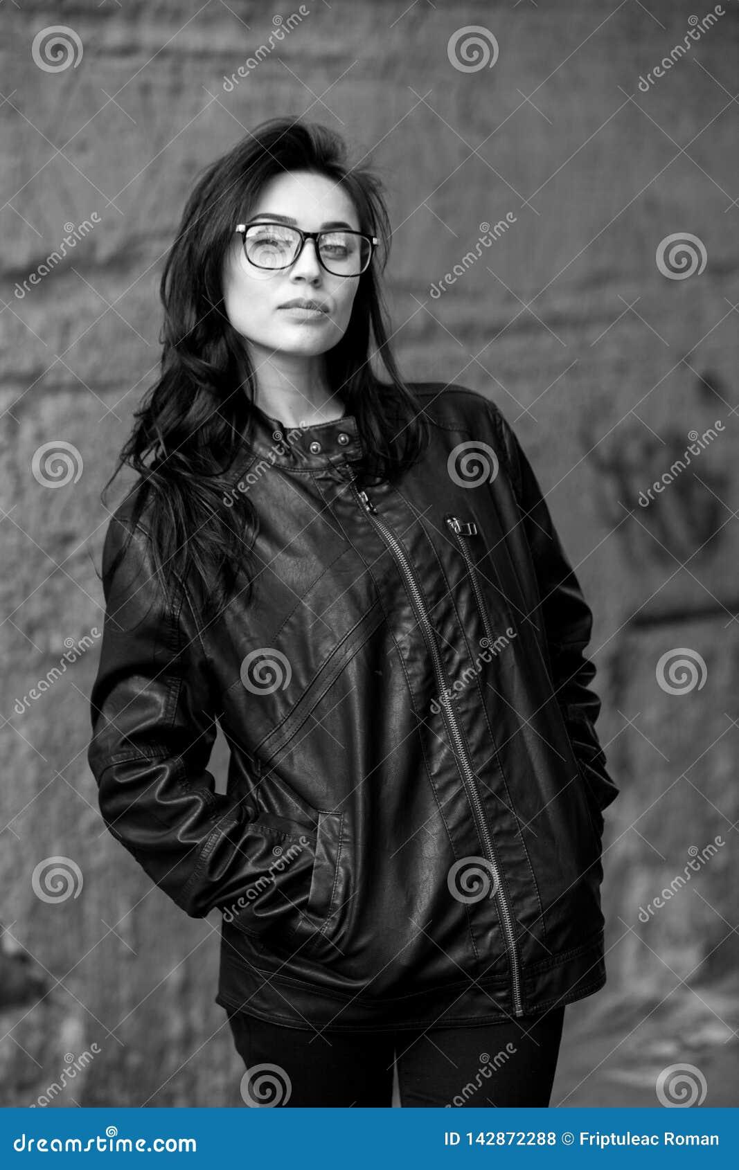 有波浪发的美女在黑皮夹克 室外逗人喜爱的新的女商人纵向
