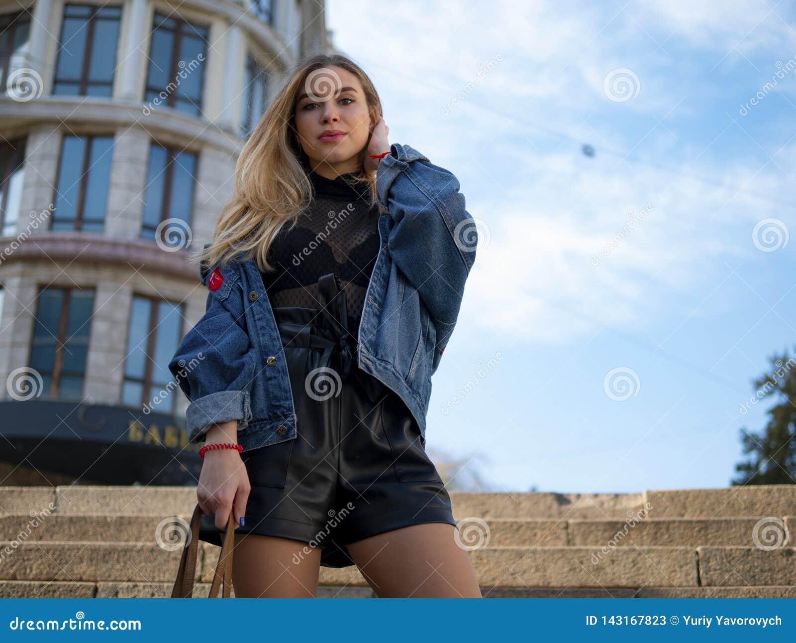有流动的头发的可爱的女孩在反对一现代大厦和天空蔚蓝的背景的一件牛仔布夹克