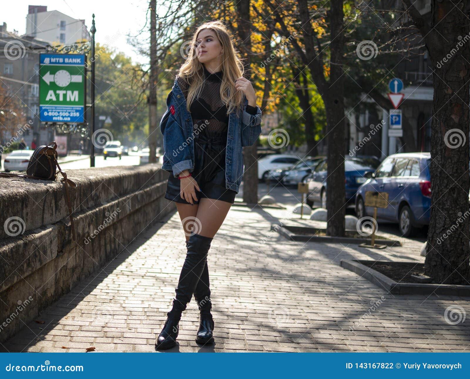 有流动的头发的可爱的金发碧眼的女人在站立在充分的成长的街道上的皮靴