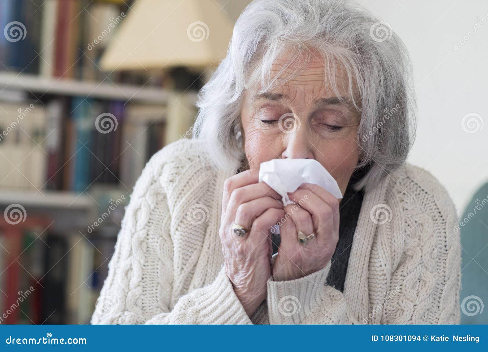 有流感吹的鼻子的资深妇女在家