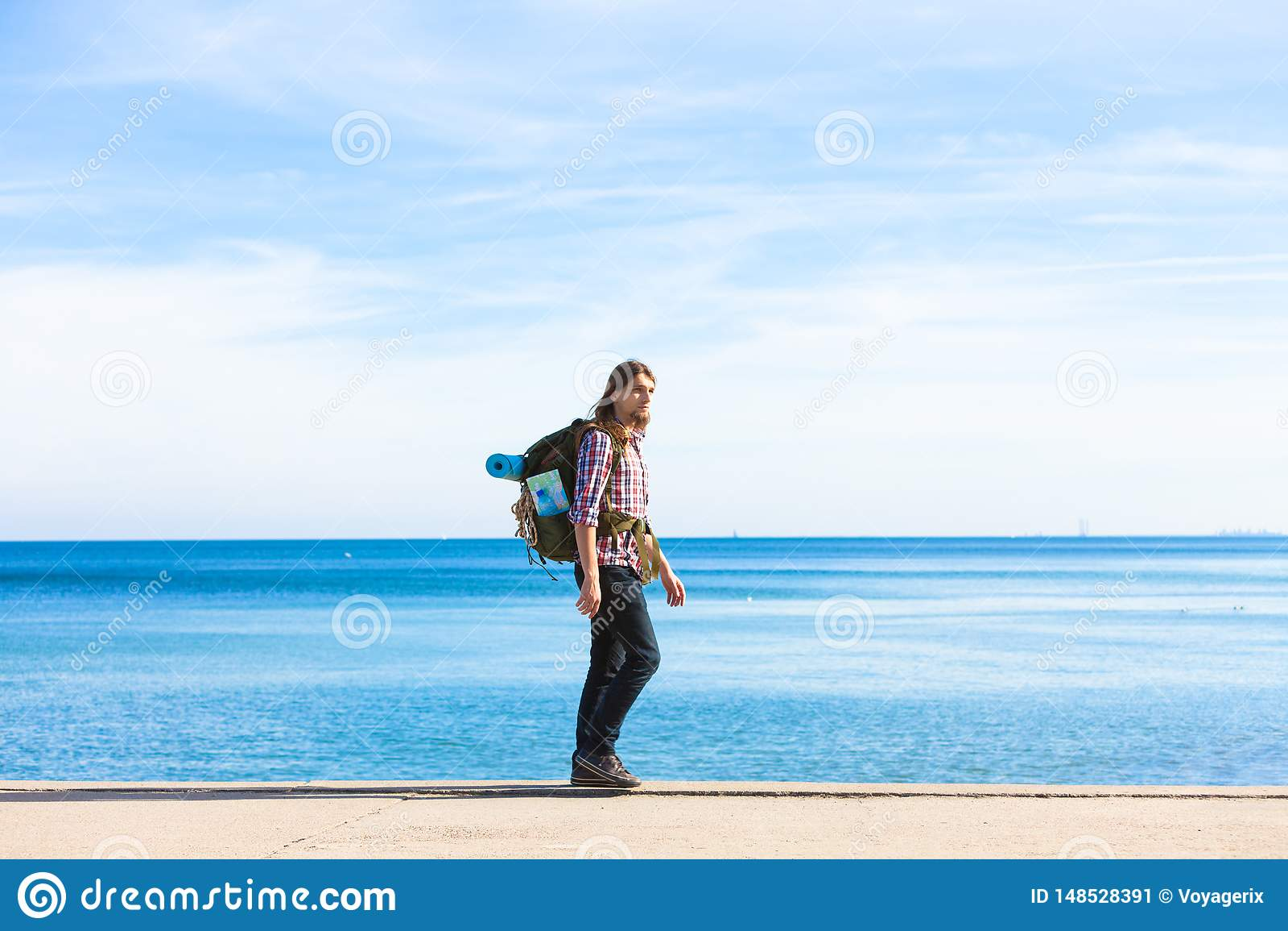 有流浪由海边的背包的人徒步旅行者