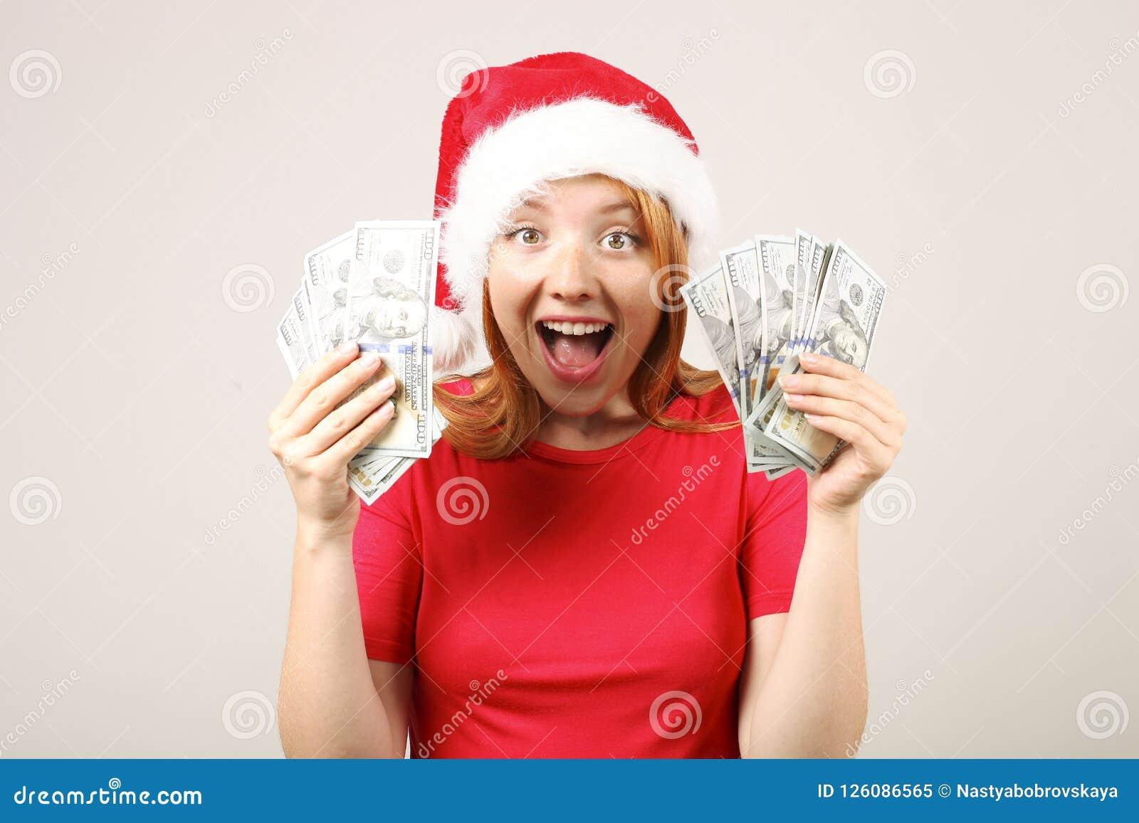有流行音乐pom的逗人喜爱的红发女性佩带的圣诞老人` s帽子,庆祝冬天欢乐季节假日