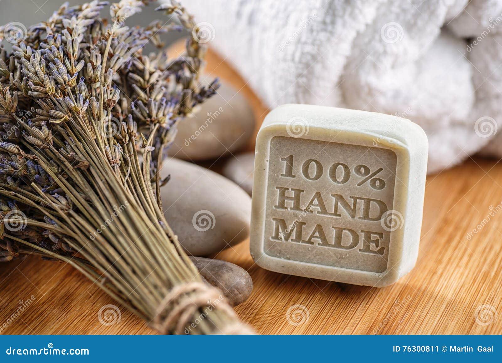 有淡紫色束和石头的手工制造化妆用品肥皂在木板,产品或身体关心
