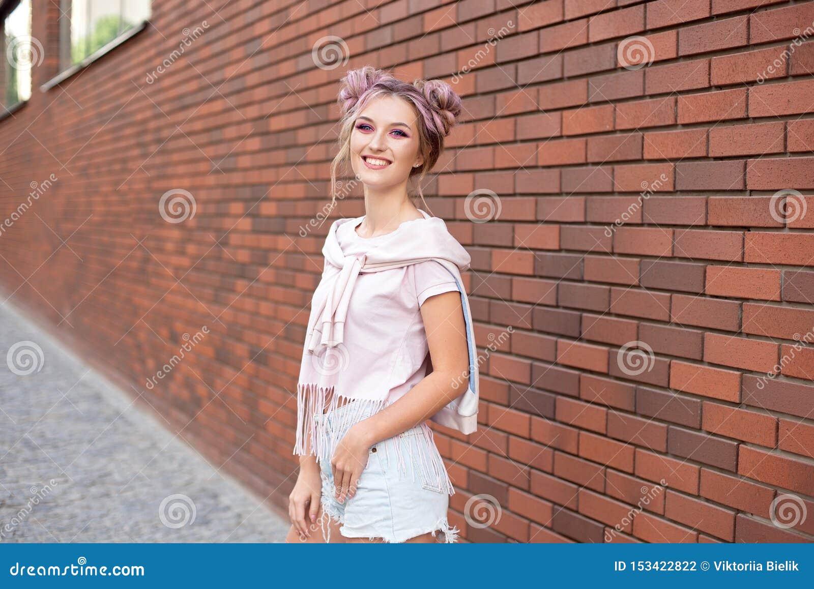 有清楚的皮肤、明亮的桃红色构成和白色牙的美丽的微笑的妇女用在红砖背景的头发小圆面包