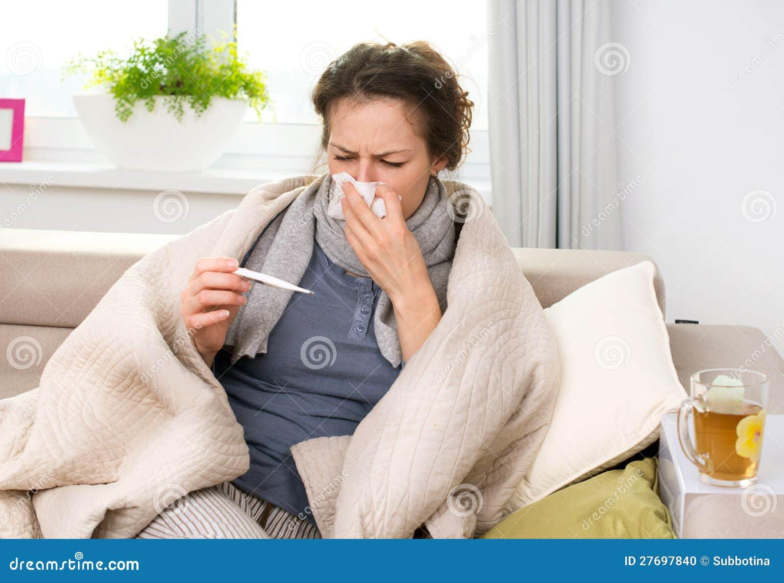 有温度计的病的妇女。 流感