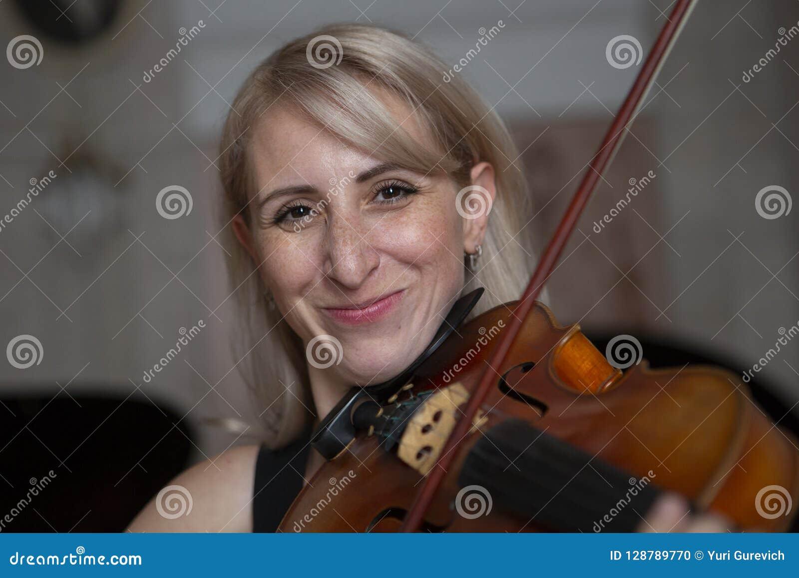 有演奏中提琴的波浪金发的年轻美丽的妇女,拿着微笑的弓盘旋在她的肩膀的仪器和, looki