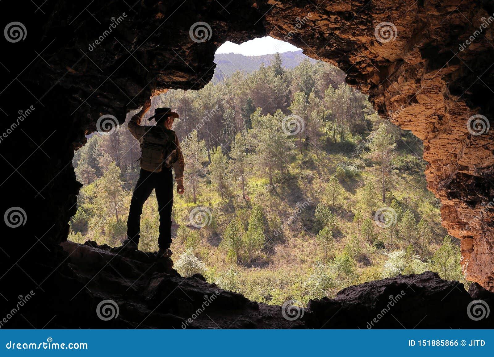 有澳大利亚帽子和背包的探险家在洞的入口观看森林的