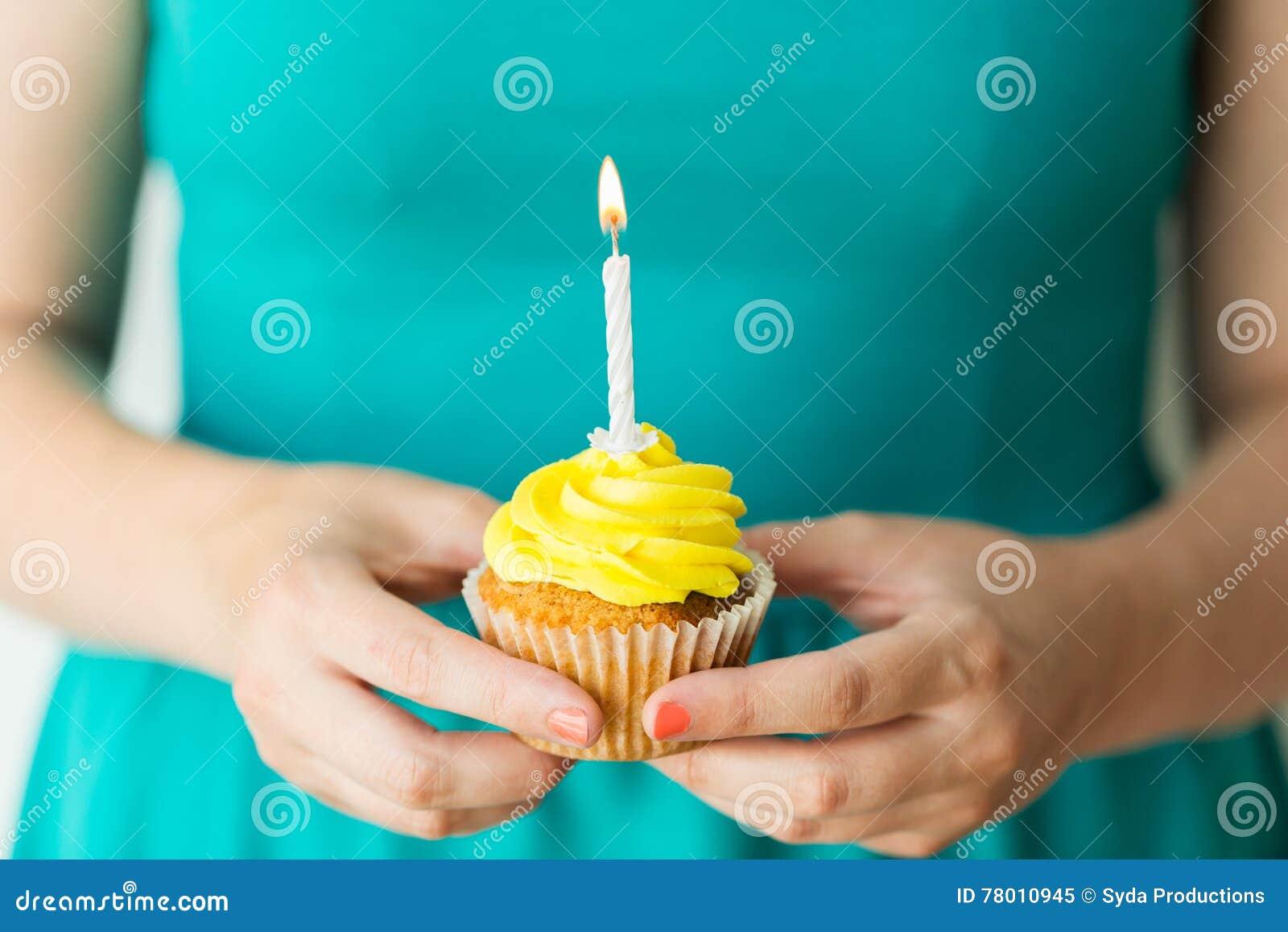 有灼烧的蜡烛的妇女在生日杯形蛋糕