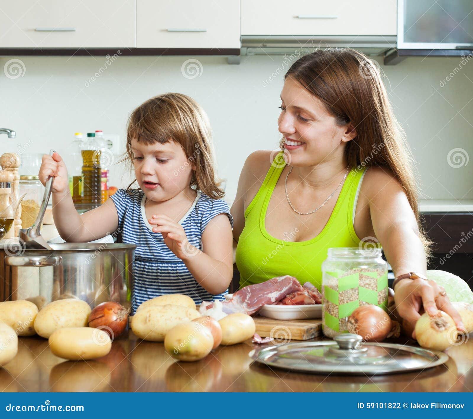 有烹调汤的孩子的母亲