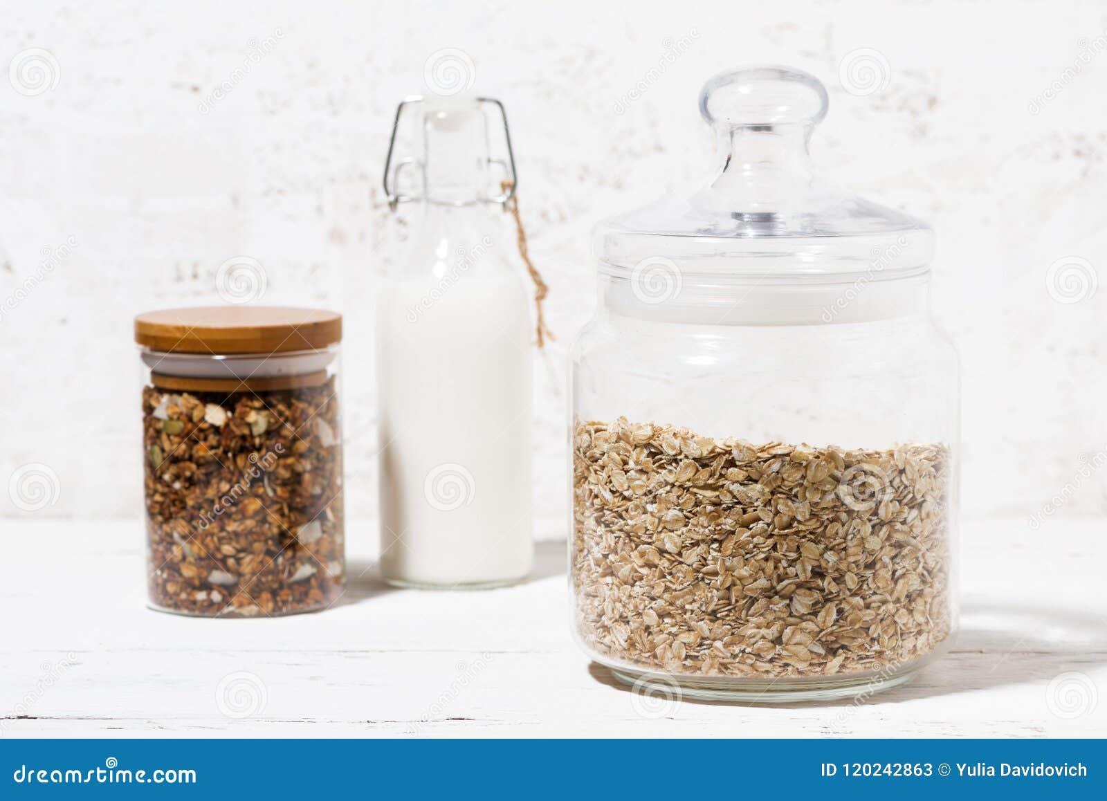 有燕麦剥落、格兰诺拉麦片和瓶的玻璃瓶子牛奶,特写镜头