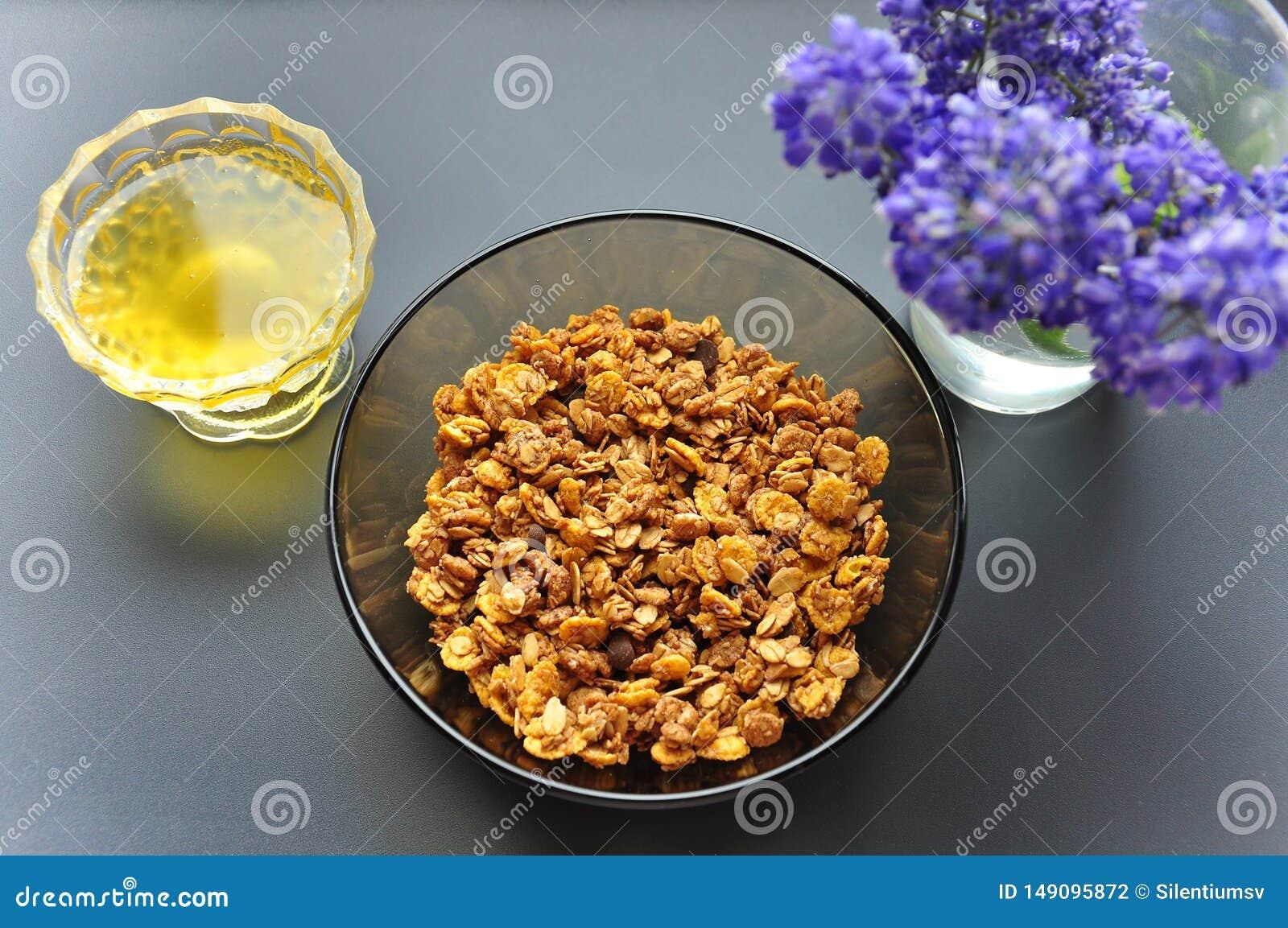 有燕麦粥和蜂蜜剥落的一个深板材碗在黑暗的背景与花 健康早餐适当的营养