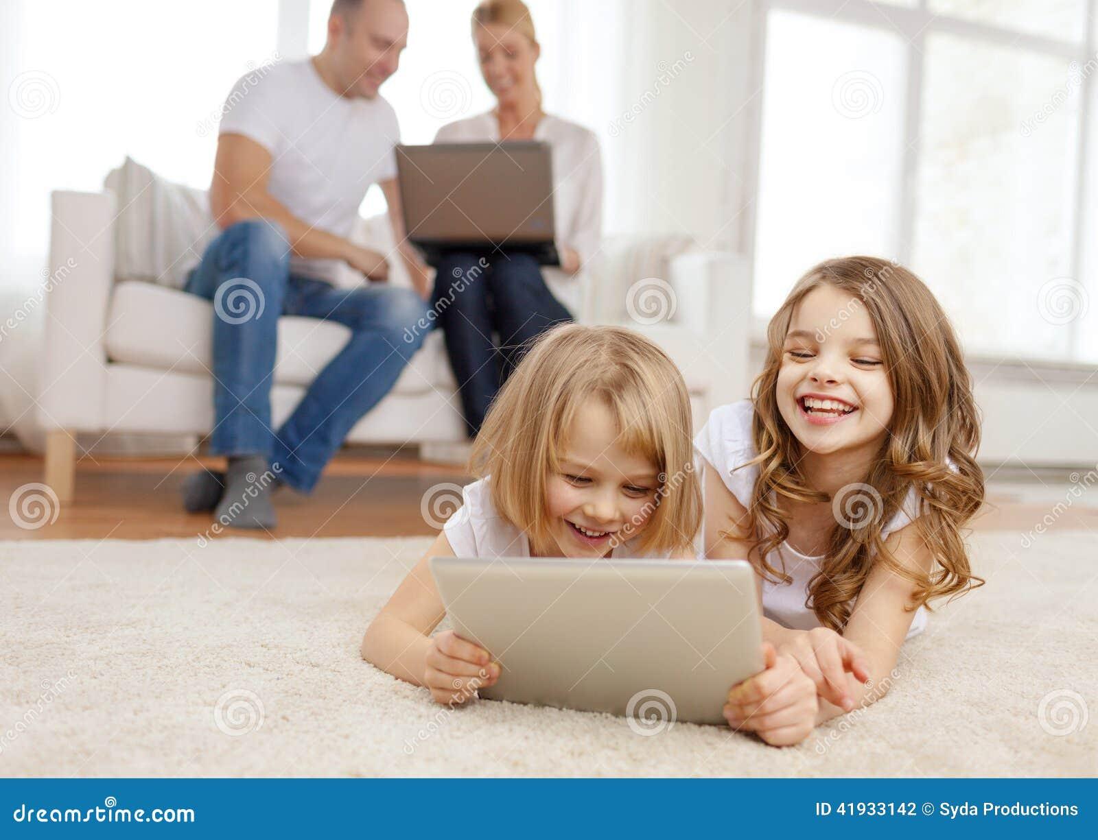 有片剂个人计算机和父母的微笑的姐妹