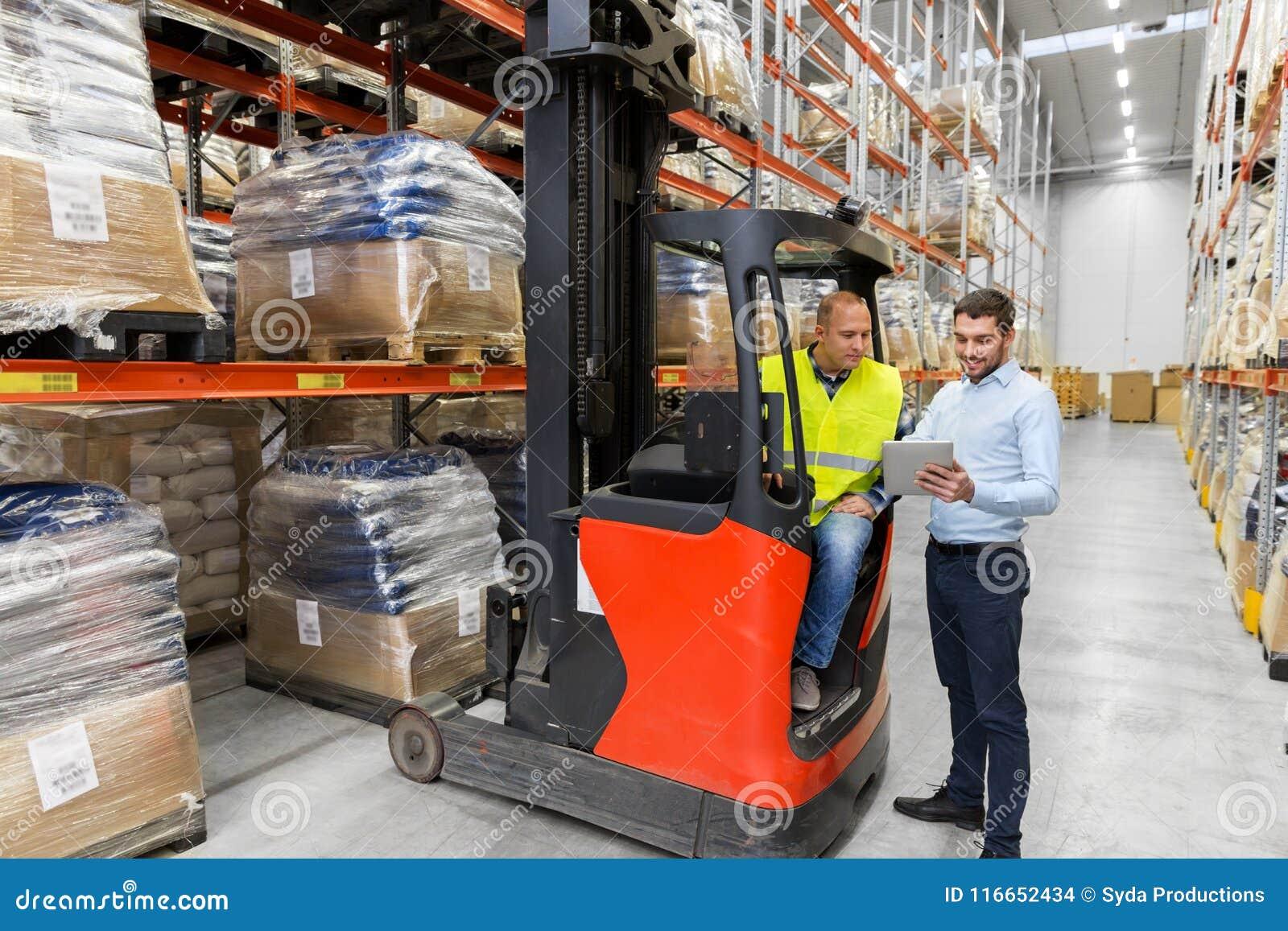 有片剂个人计算机和铲车的人在仓库