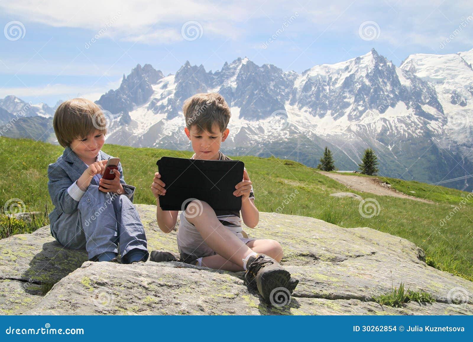 有片剂个人计算机的二个男孩在阿尔卑斯