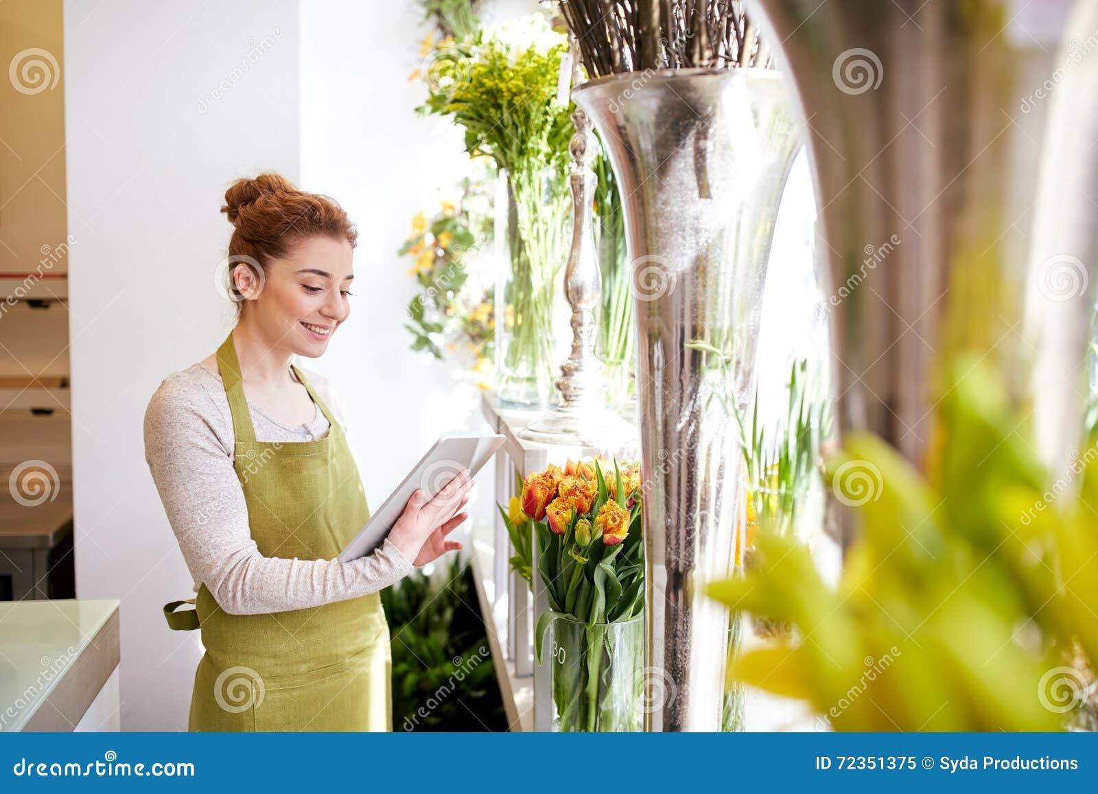 有片剂个人计算机计算机的妇女在花店