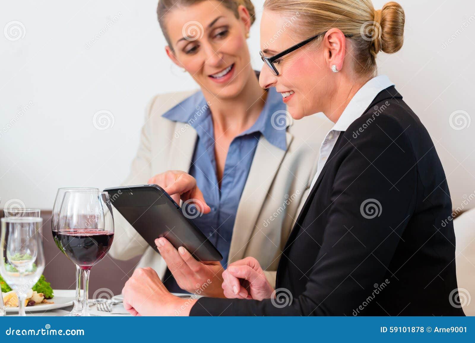 有片剂的两个商人吃午餐的