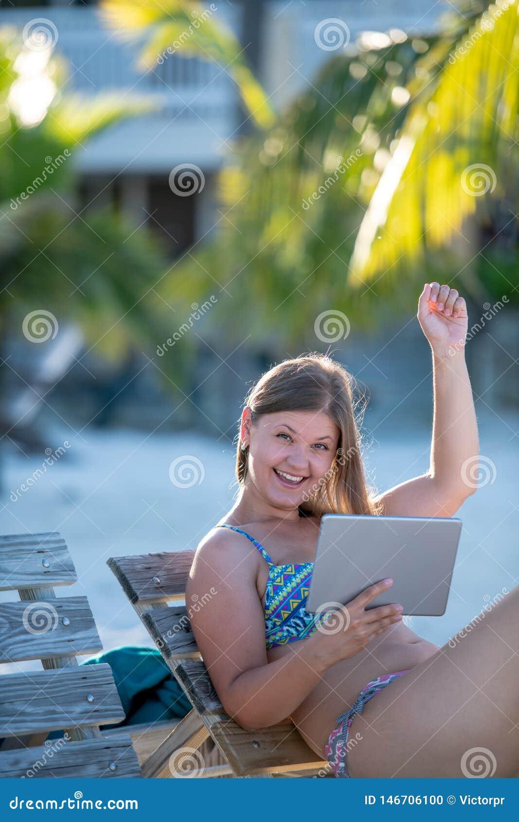 有片剂的愉快的年轻女人在海滩
