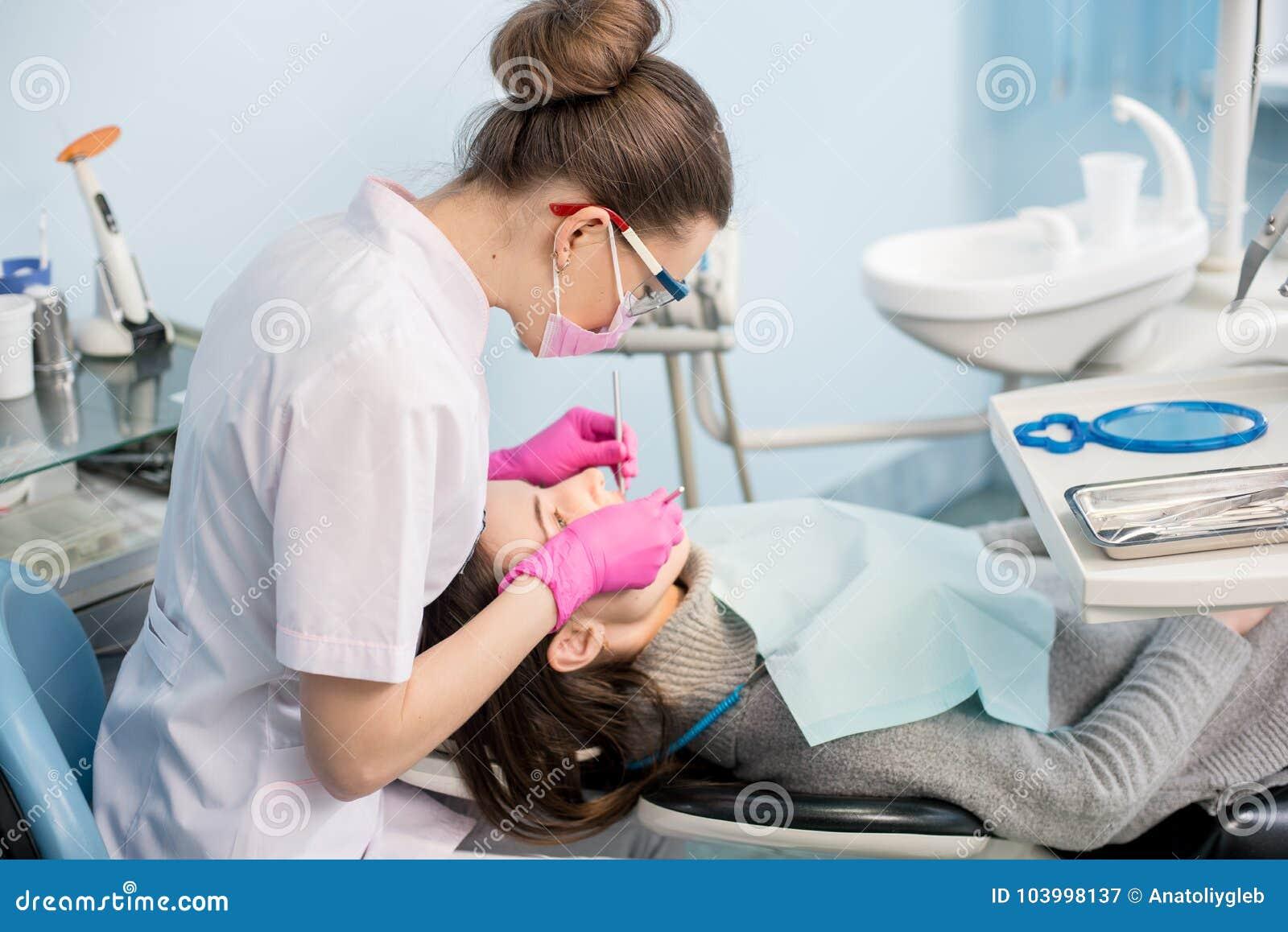 有牙齿工具的女性牙医-在牙齿诊所办公室反映并且探查对待耐心牙