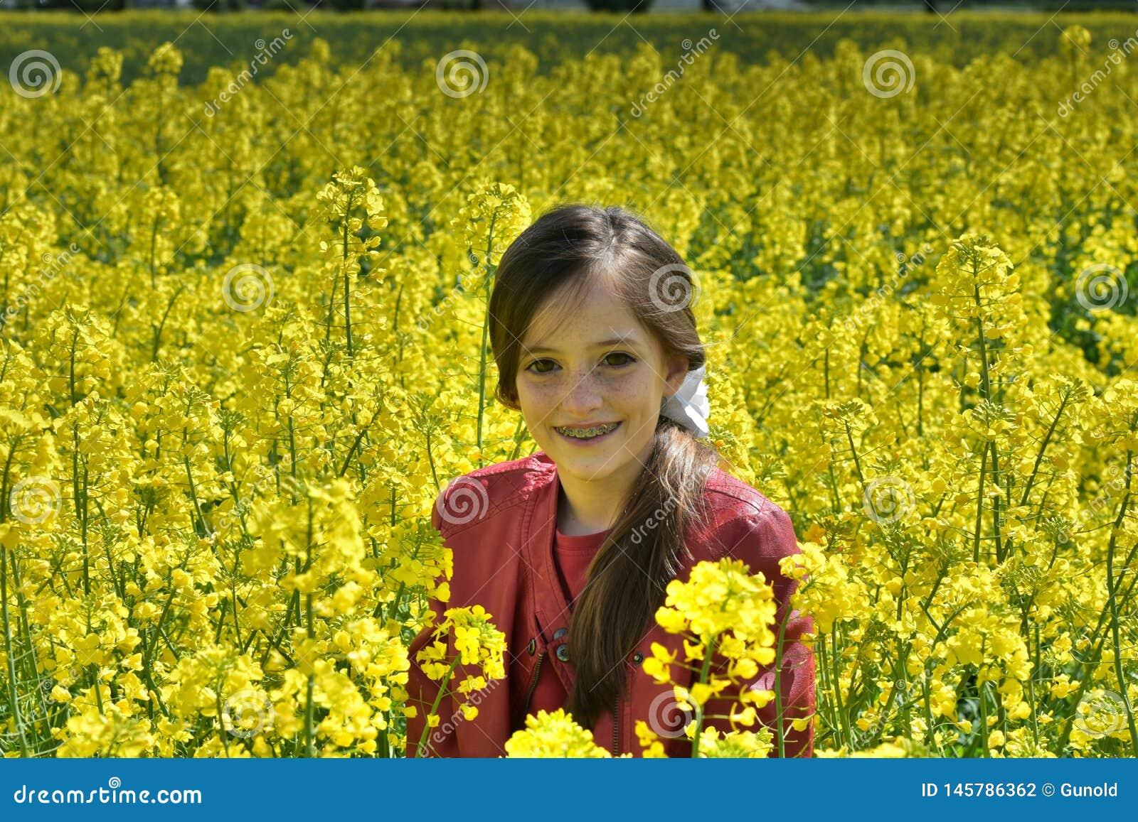 有牙齿括号的女孩在与黄色花的一个领域