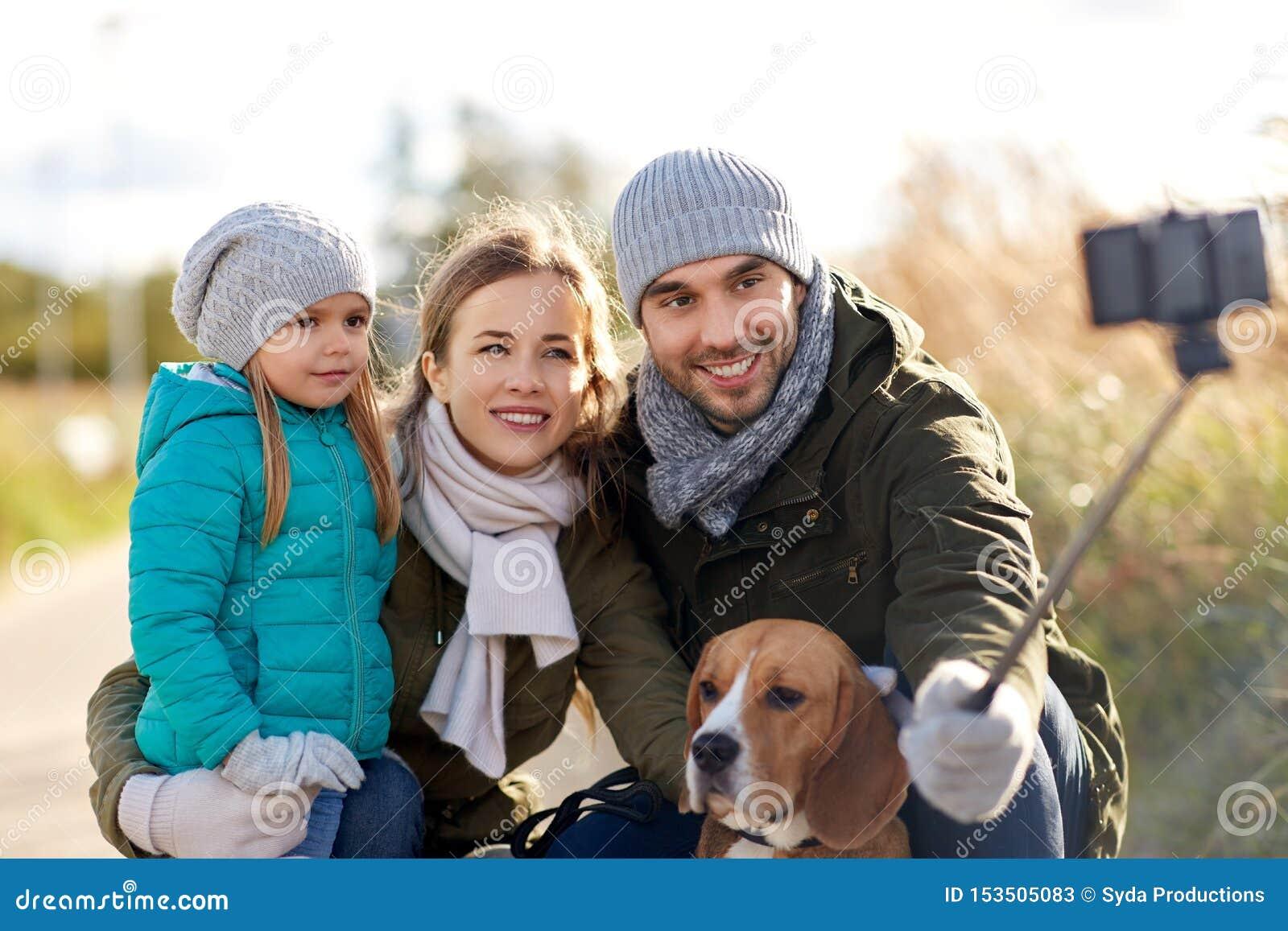 有狗的幸福家庭在秋天的采取selfie