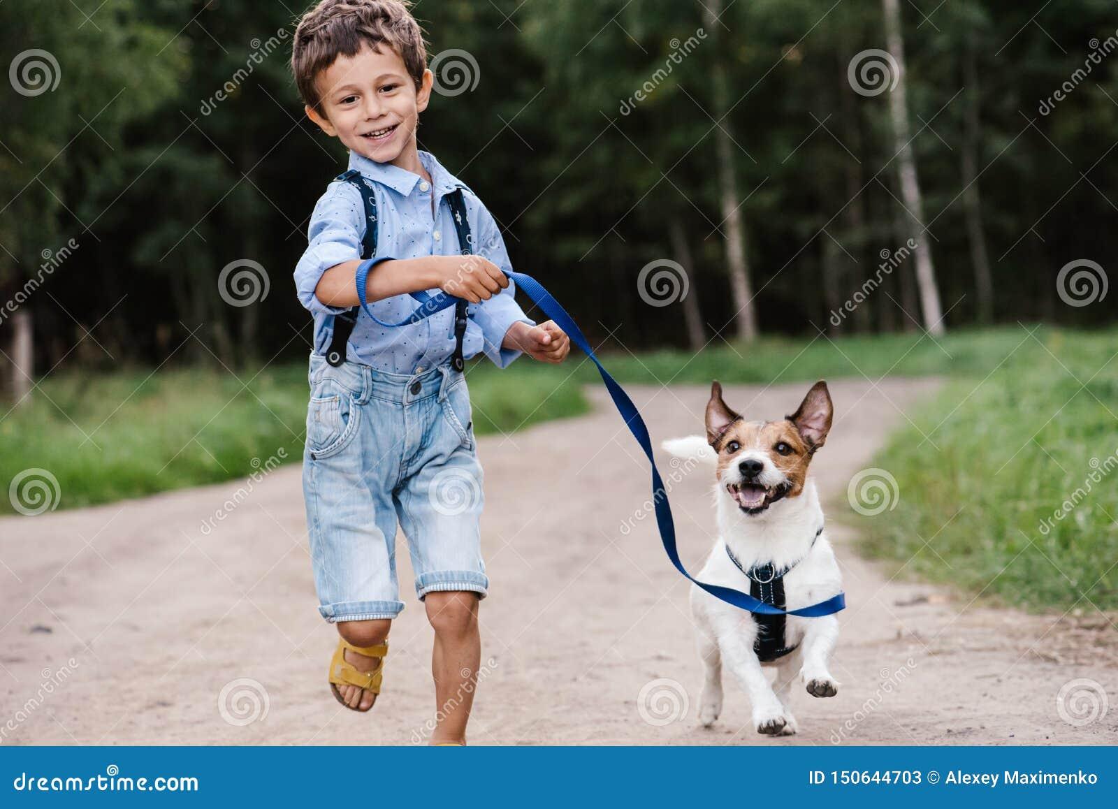 有狗的愉快的男孩在运行在乡下公路的皮带