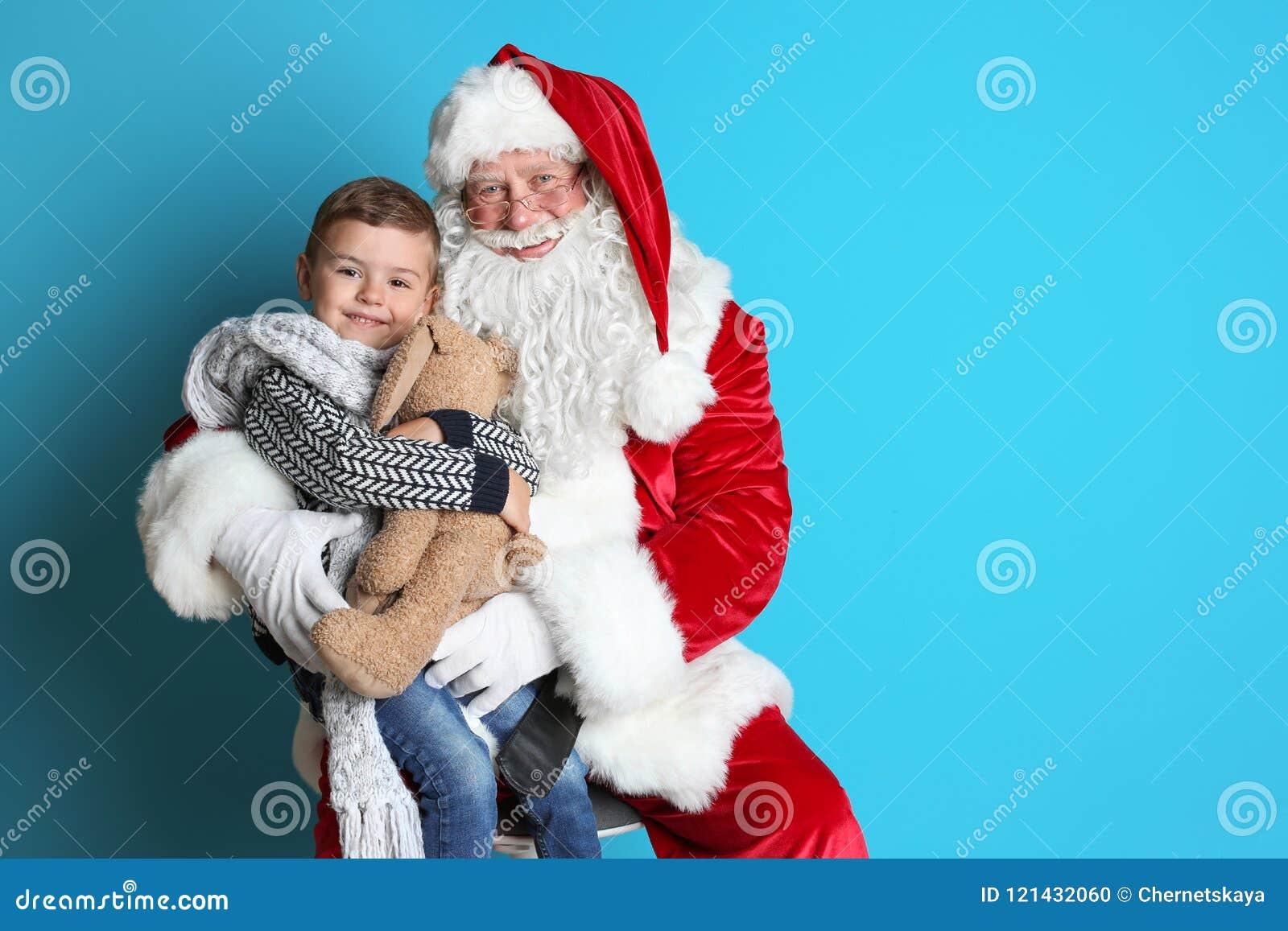 有玩具兔宝宝的小男孩坐地道圣诞老人`膝部