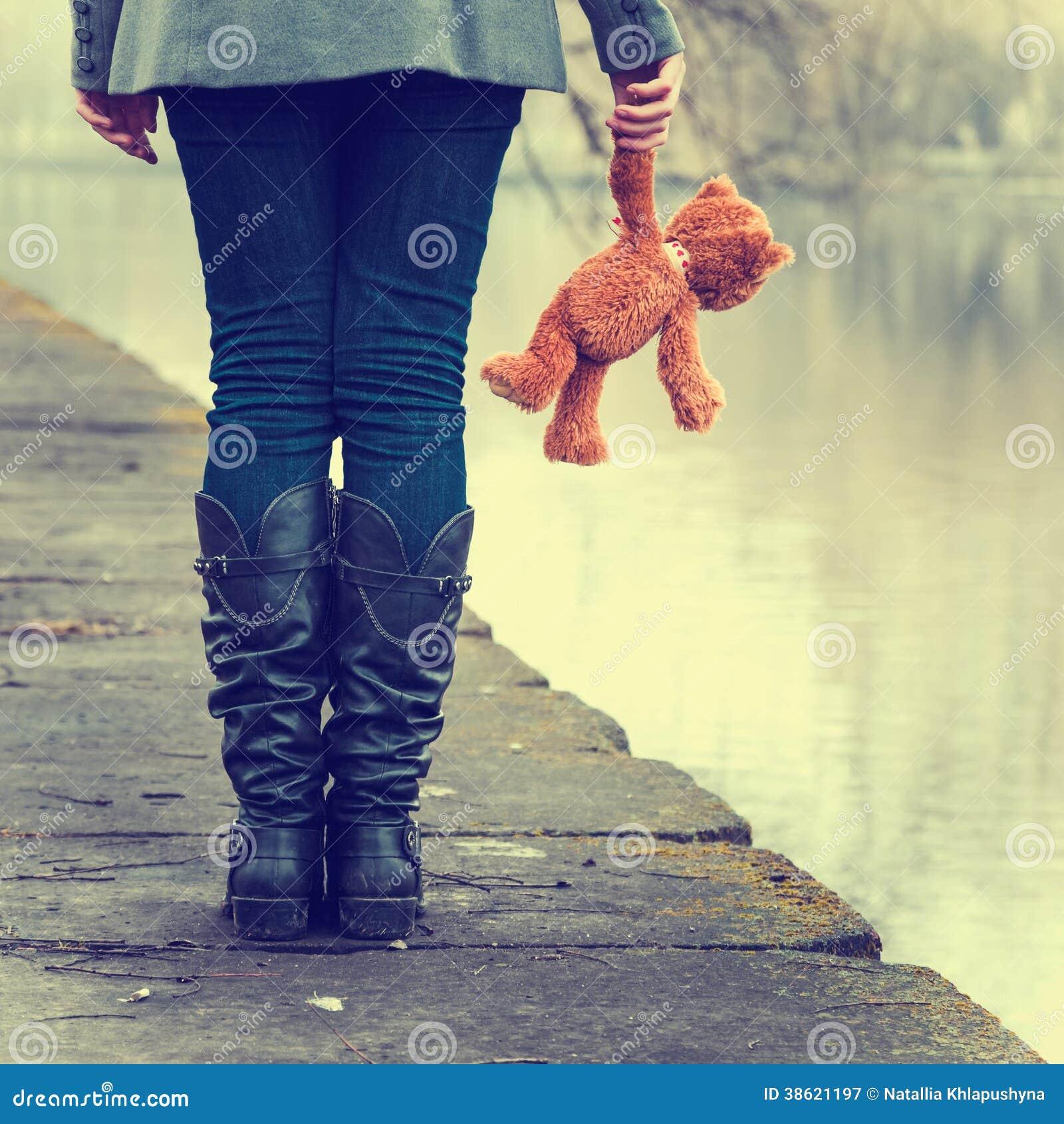 有玩具熊的孤独的女孩在河附近