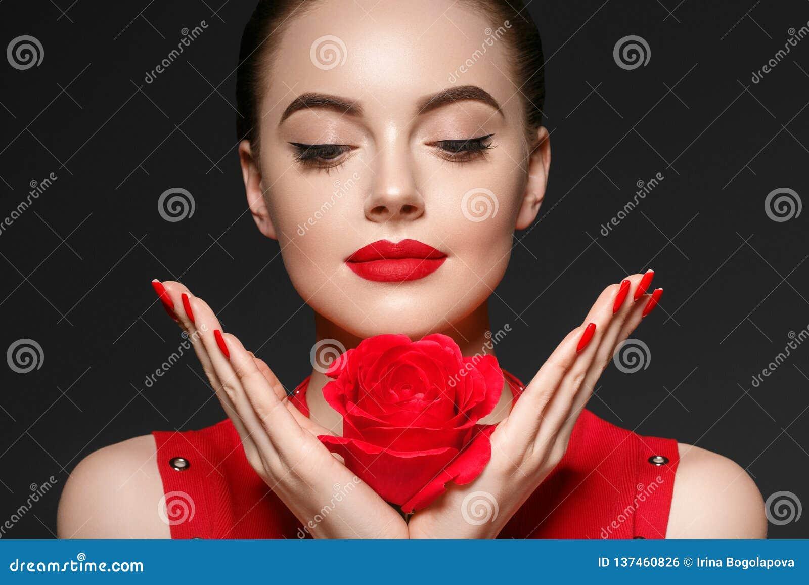 有玫瑰色花美丽的卷发和嘴唇的秀丽妇女