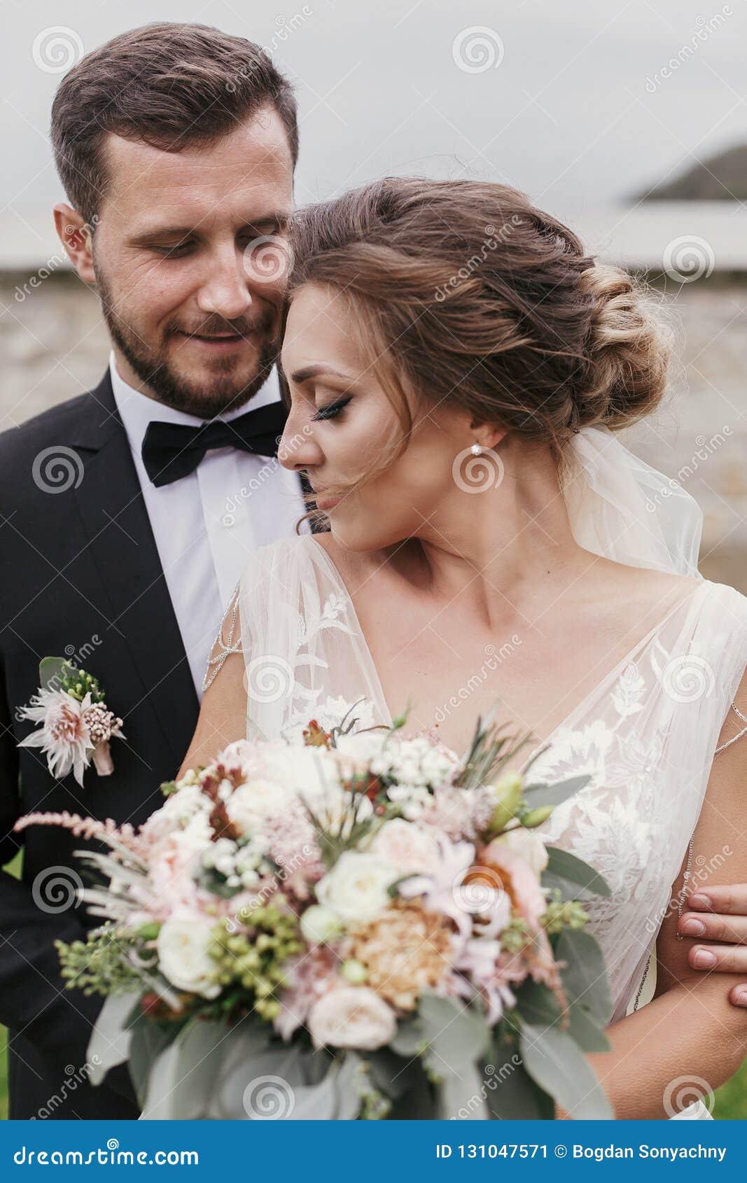 有现代花束和时髦的柔和新郎hugg的华美的新娘