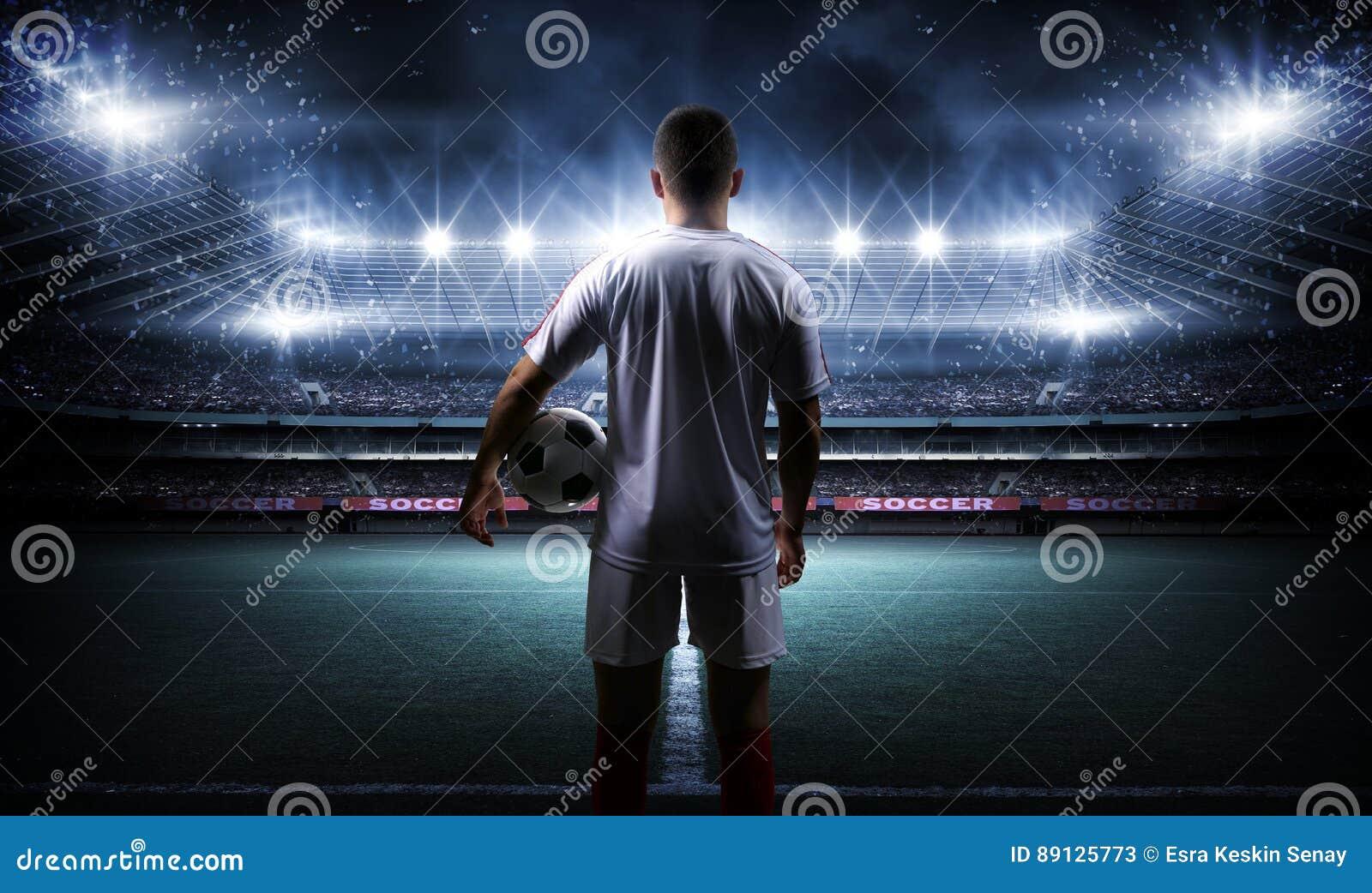 有球的足球运动员在体育场的领域