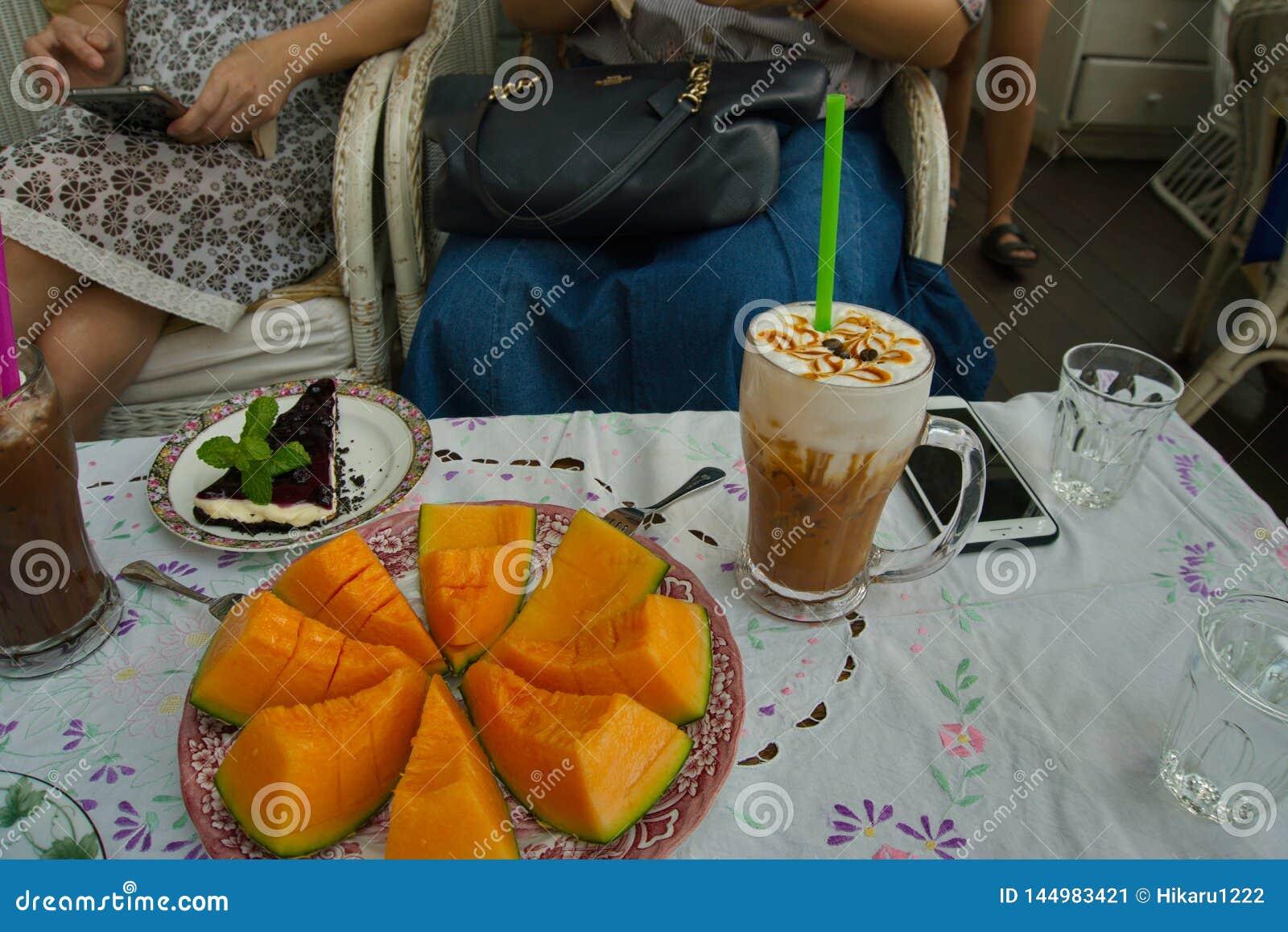 有甜瓜瓜切片,一杯冰焦糖拿铁咖啡,并且蓝莓乳酪蛋糕片断在桌上